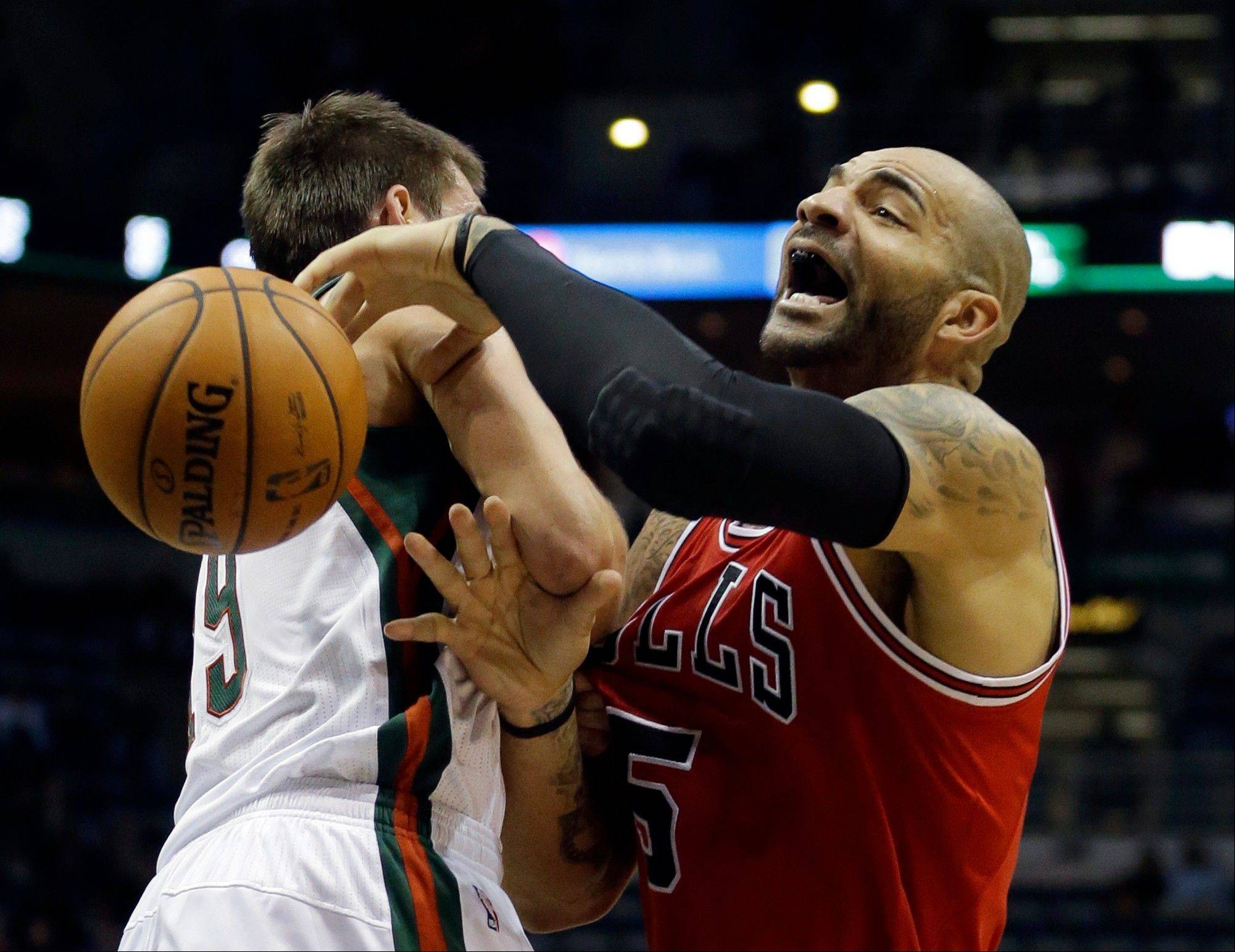 Bulls forward Carlos Boozer is fouled by the Milwaukee Bucks' Beno Udrih as he goes up for a shot Satudray during the first half in Milwaukee.