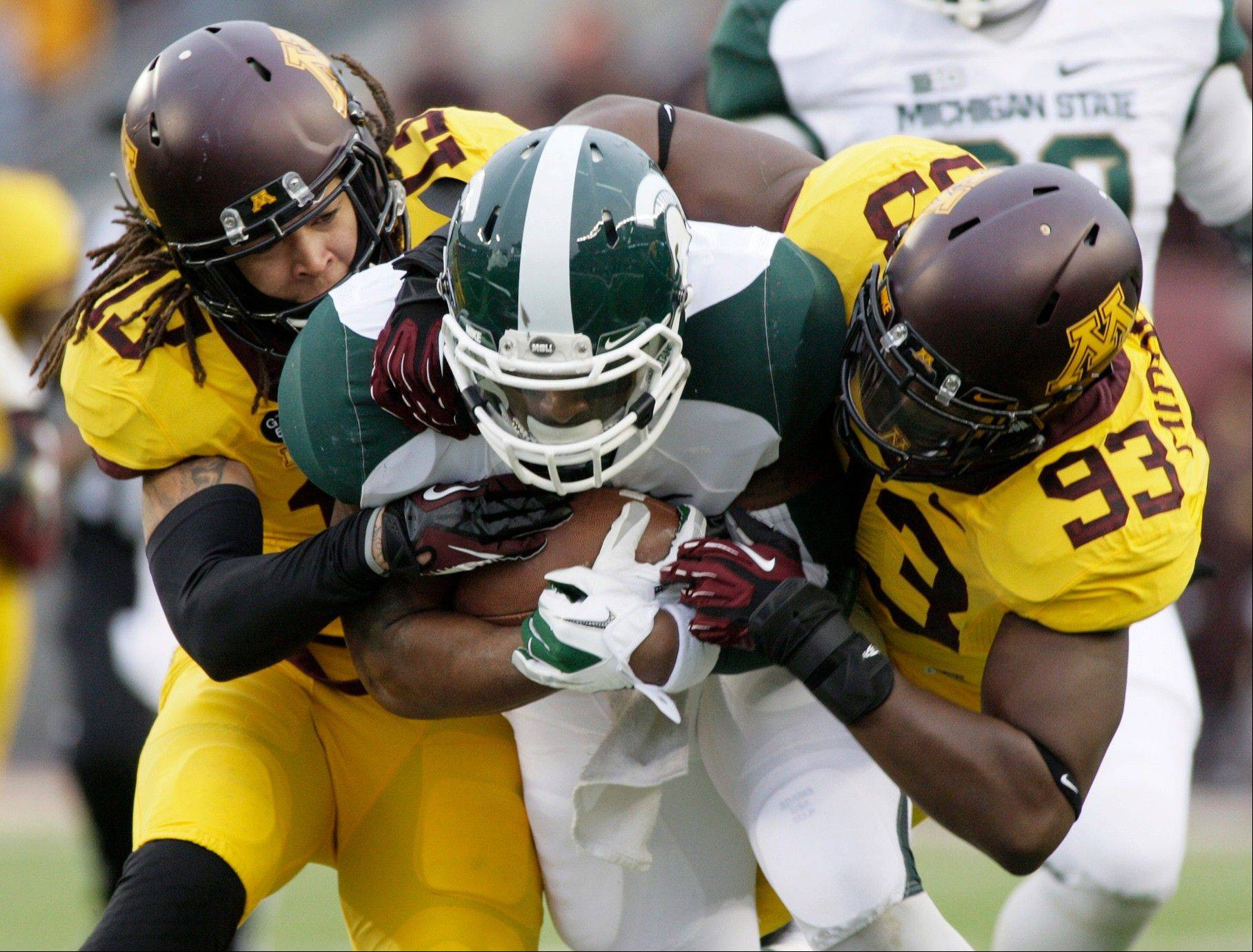 Michigan State running back Le'Veon Bell is tackled by Minnesota defensive back Derrick Wells and defensive end Ben Perry after a 40-yard run Saturday during the first half in Minneapolis.