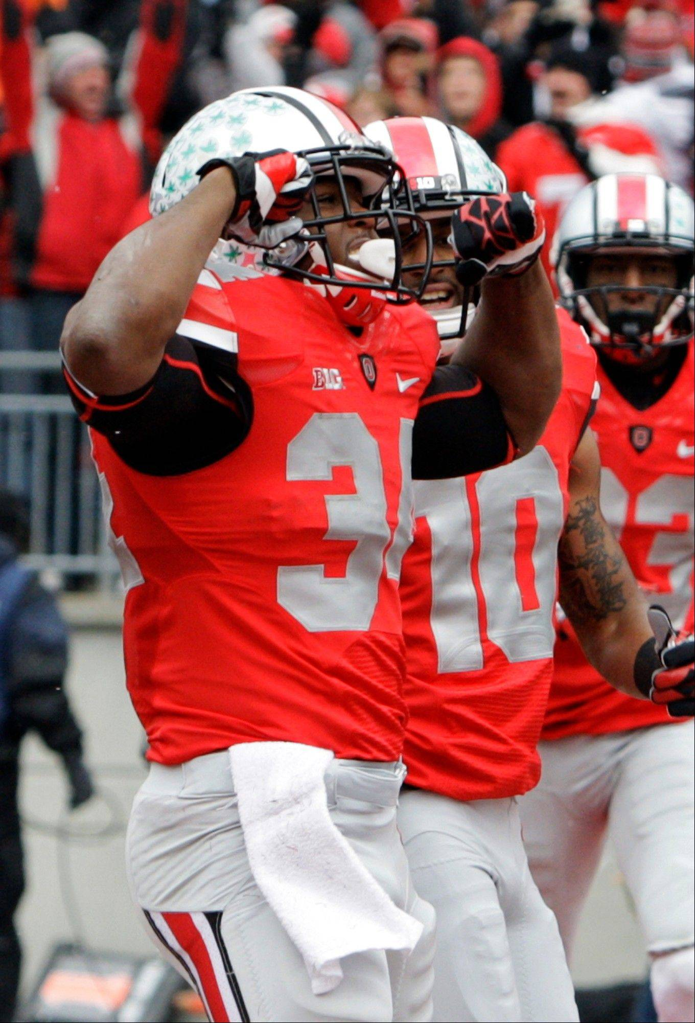 Ohio State running back Carlos Hyde celebrates after a 3-yard touchdown run against Michigan Saturday during the first quarter in Columbus.
