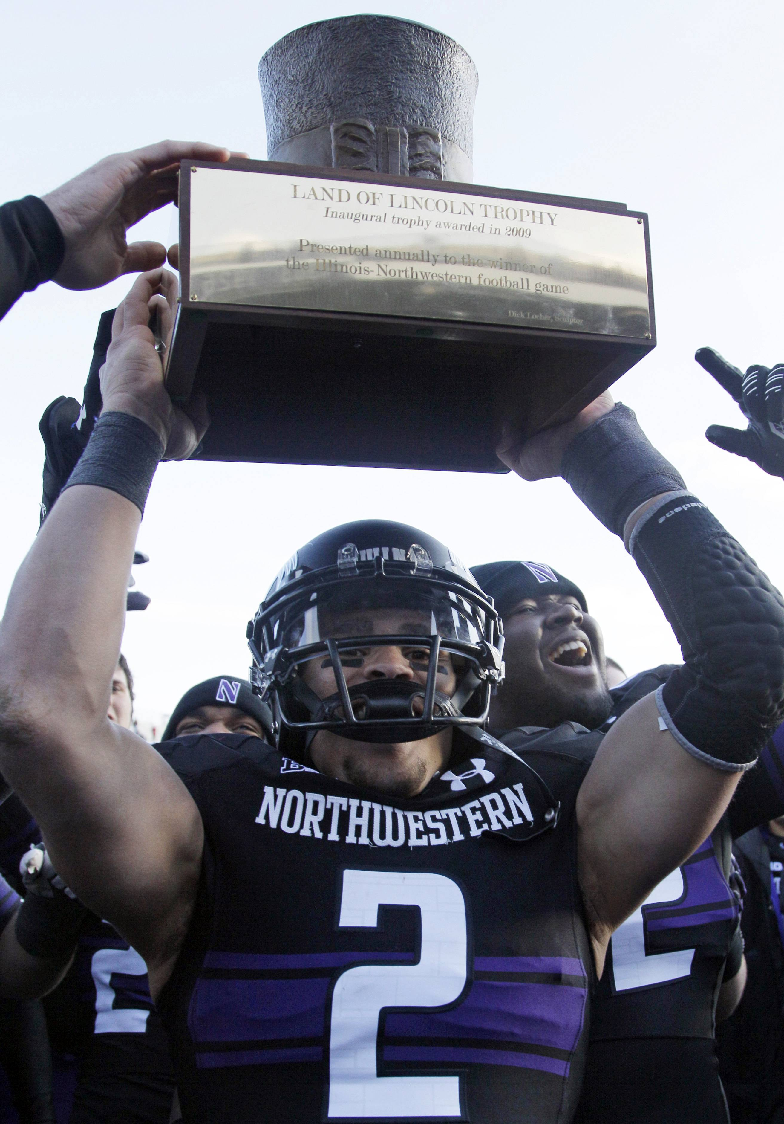 "Northwestern quarterback Kain Colter holds up the ""Land of Lincoln"" trophy Saturday as he celebrates with teammates after Northwestern defeated Illinois 50-14 in Evanston."
