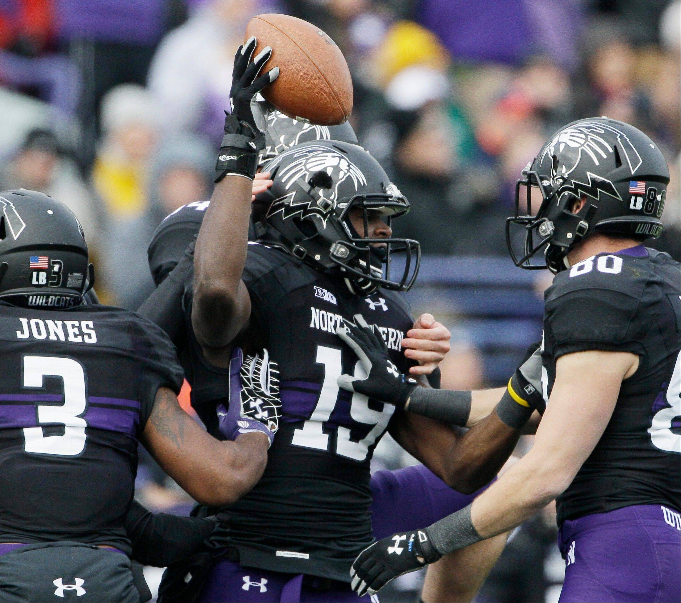 Northwestern wide receiver Cameron Dickerson (19) celebrates with teammates after recovering a fumble by Illinois defensive back Justin Green (26) Saturday during the first half in Evanston.