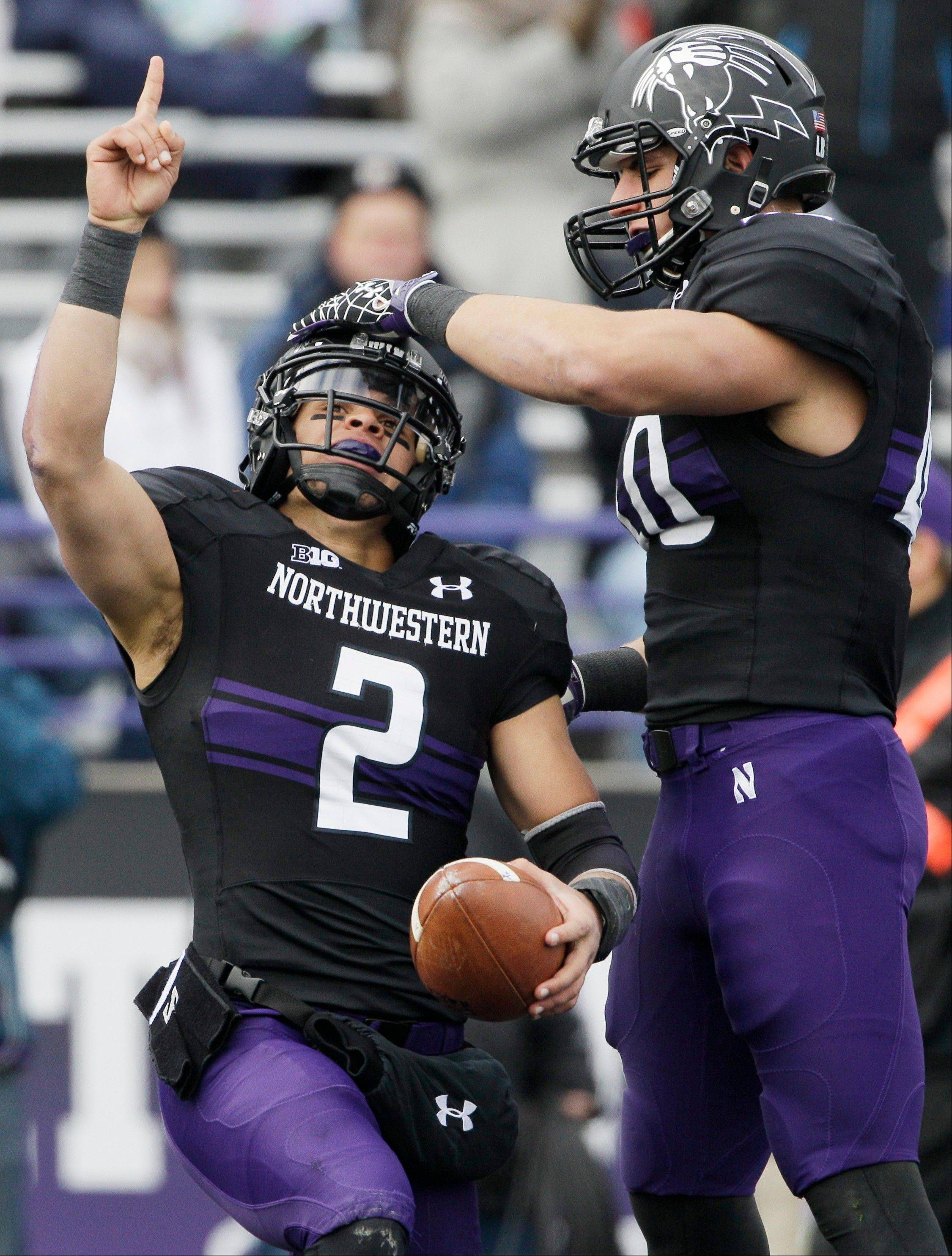 Northwestern quarterback Kain Colter (2) points as he celebrates with slotback Dan Vitale (40) Saturday after scoring a touchdown during the first half oagainst Illinois in Evanston.