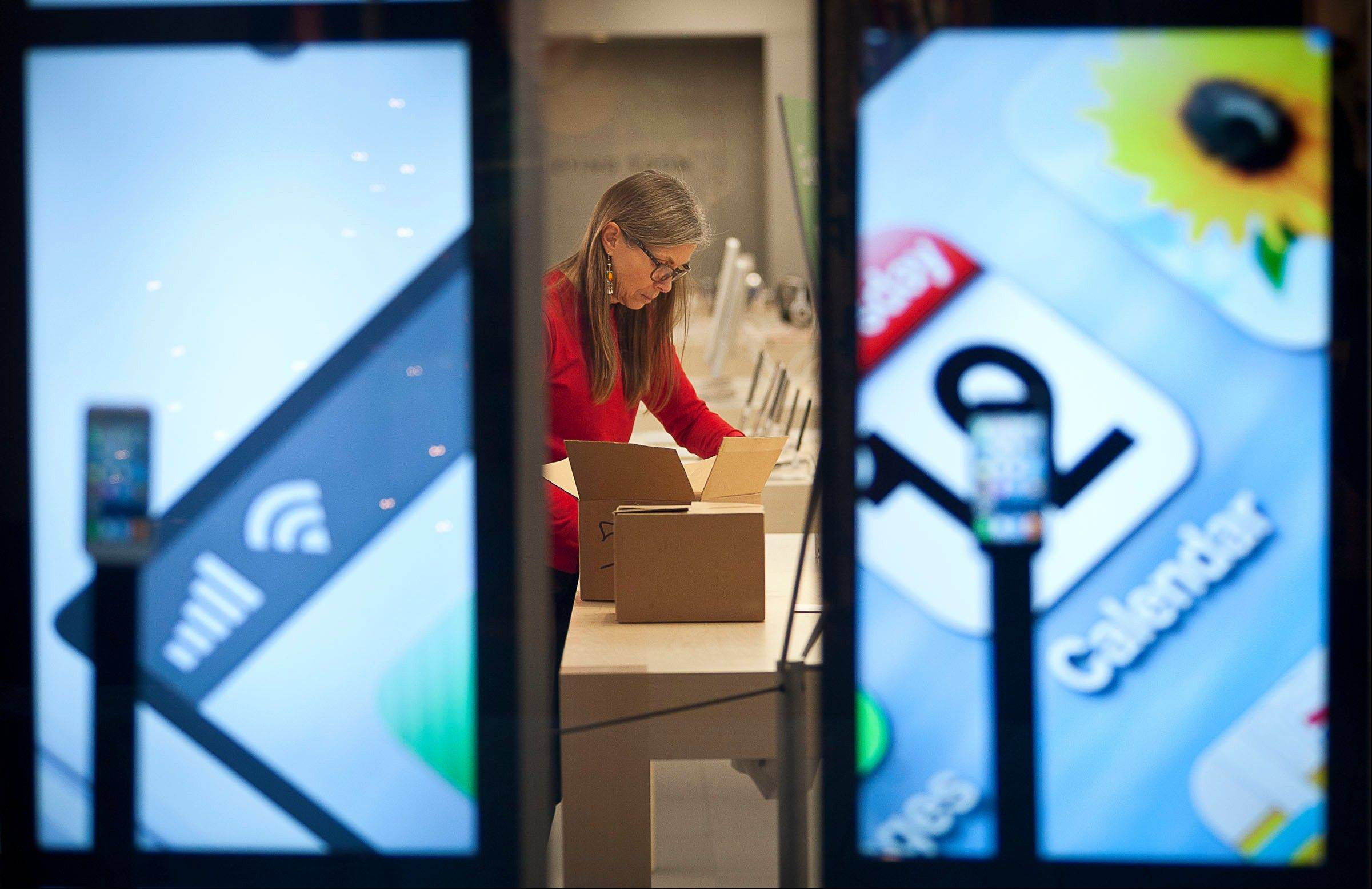 An Apple store employee unboxes iPods at the City Creek Shopping Center on Black Friday in Salt Lake City on Friday.