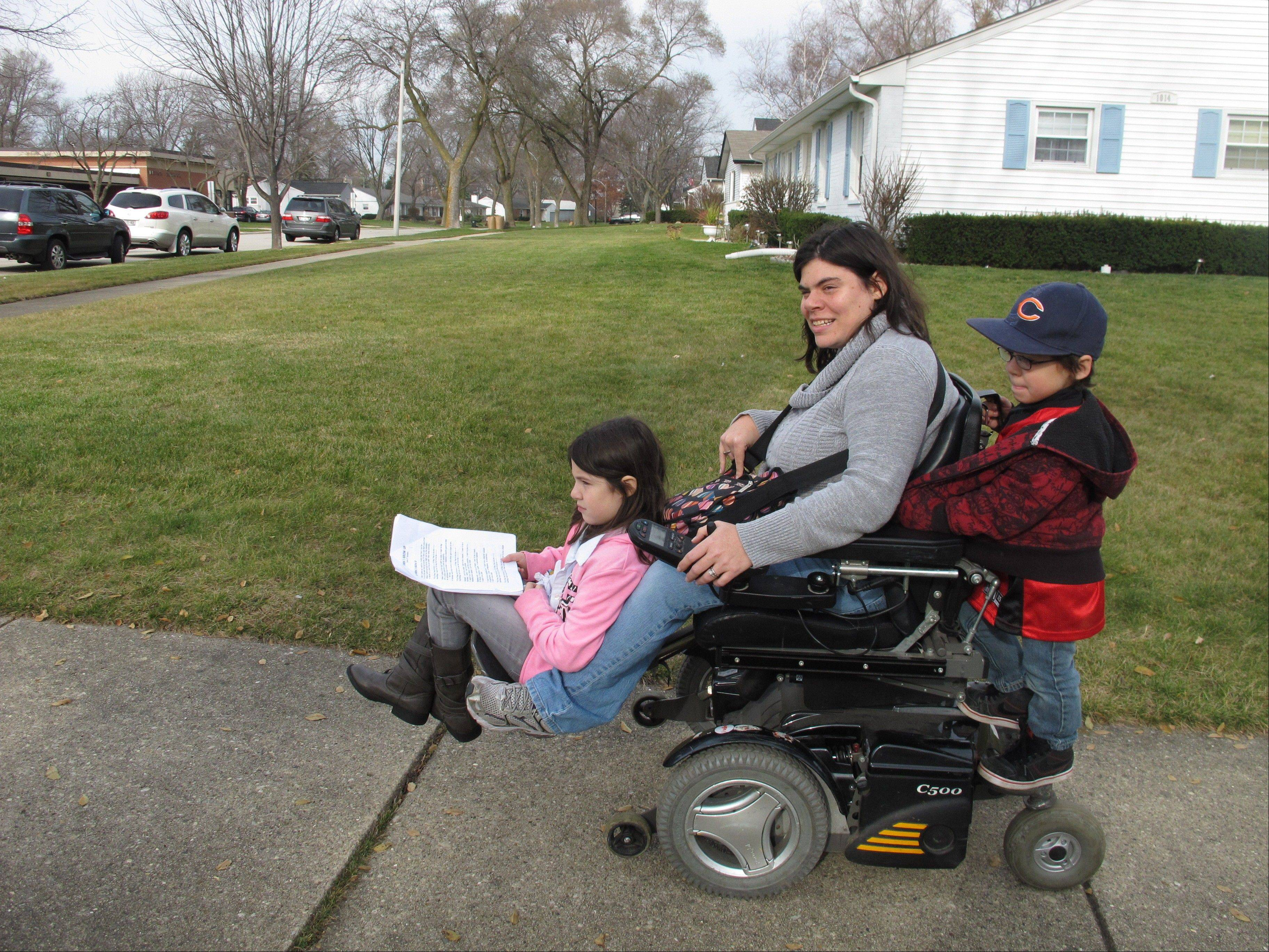 Twins Abigail and Noah Thomas, 8, ride on the motorized wheelchair of their mother, Jenn Thomas, on their way to a schoolbook fair in Arlington Heights. Thomas, a 36-year-old mom who has cerebral palsy, says her twins occasionally complain about having to do a few extra chores around the house to help her.