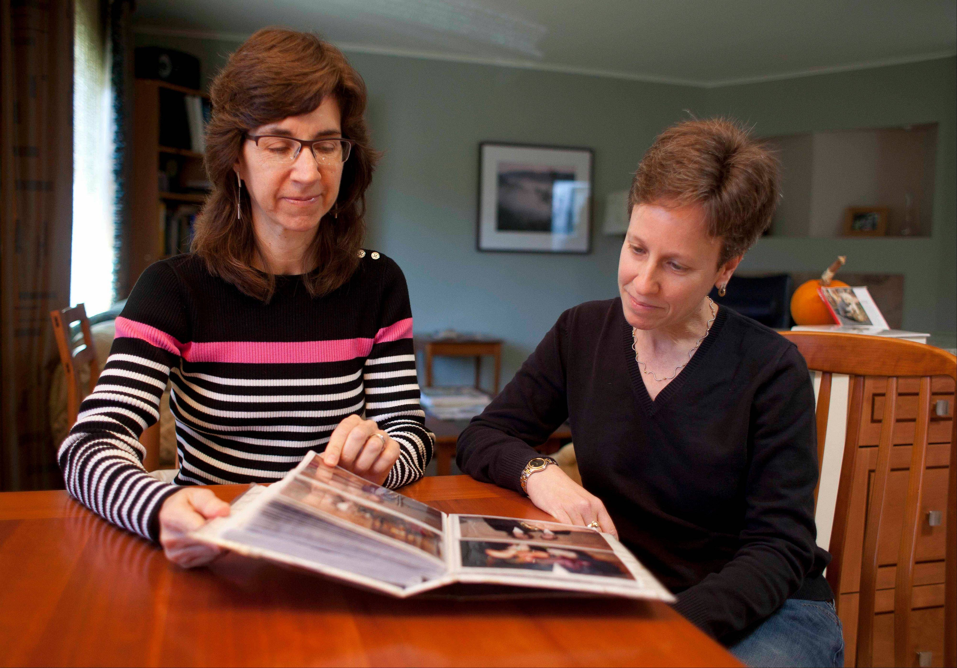 Karen Golinski, left, and Amy Cunninghis, look over a photo album of their wedding photos in San Francisco. All Golinski wanted was to enroll her spouse in her employer-sponsored health plan. Four years later, her request still is being debated.