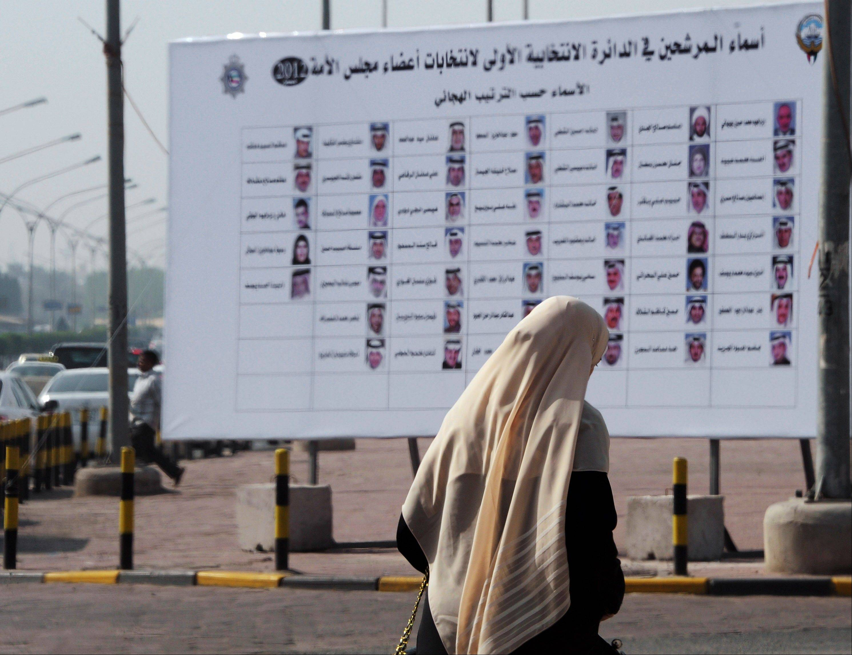 A Kuwaiti woman walks past a board with the names and photos of next December�s election candidates in Salwa, Kuwait. The past year has brought almost nonstop � and highly complex � political turmoil.