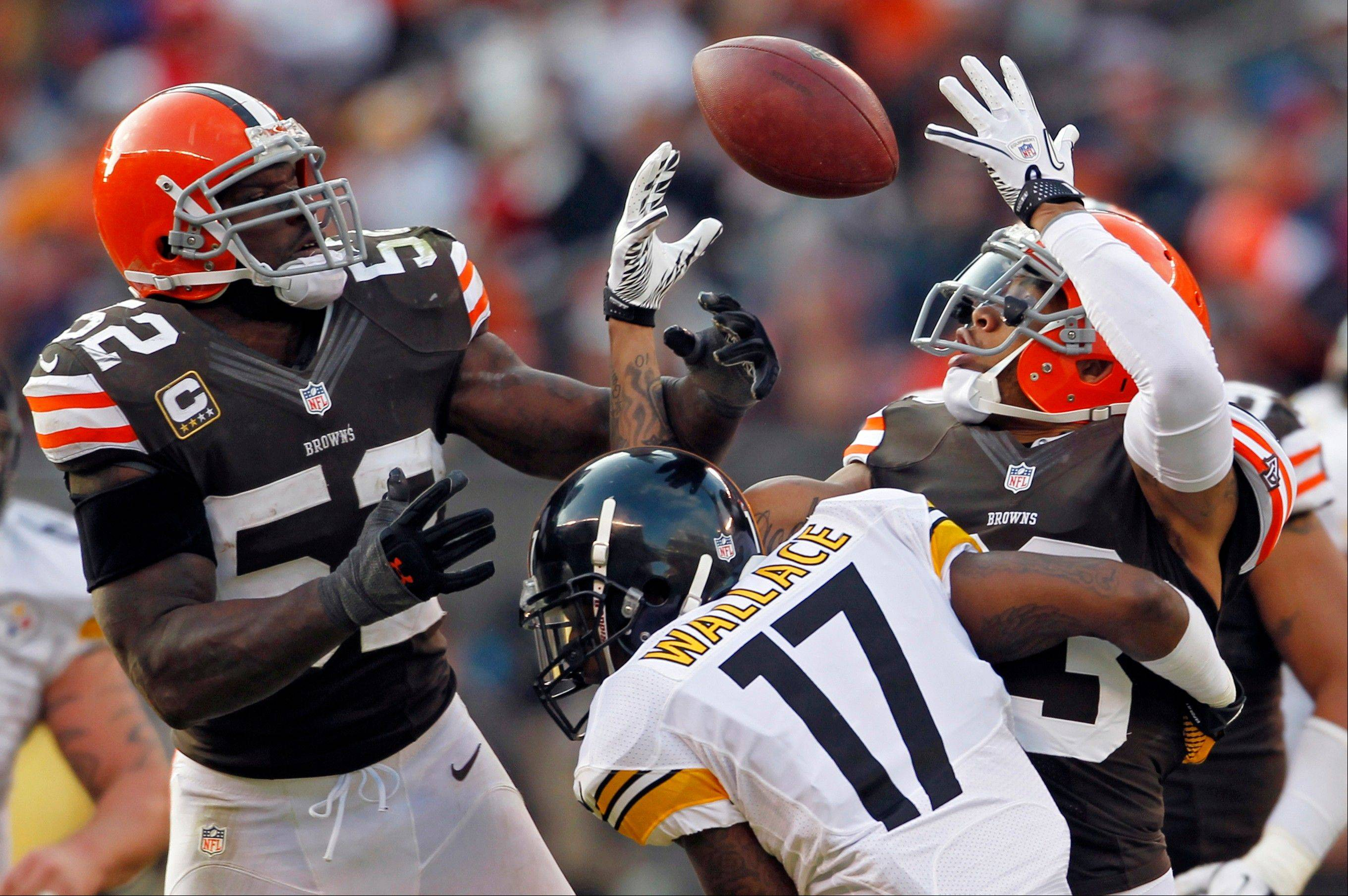 Cleveland Browns linebacker D�Qwell Jackson (52) and cornerback Joe Haden break up a pass to Pittsburgh Steelers wide receiver Mike Wallace in the fourth quarter Sunday in Cleveland. The tipped ball was recovered by Browns defensive tackle Billy Winn.
