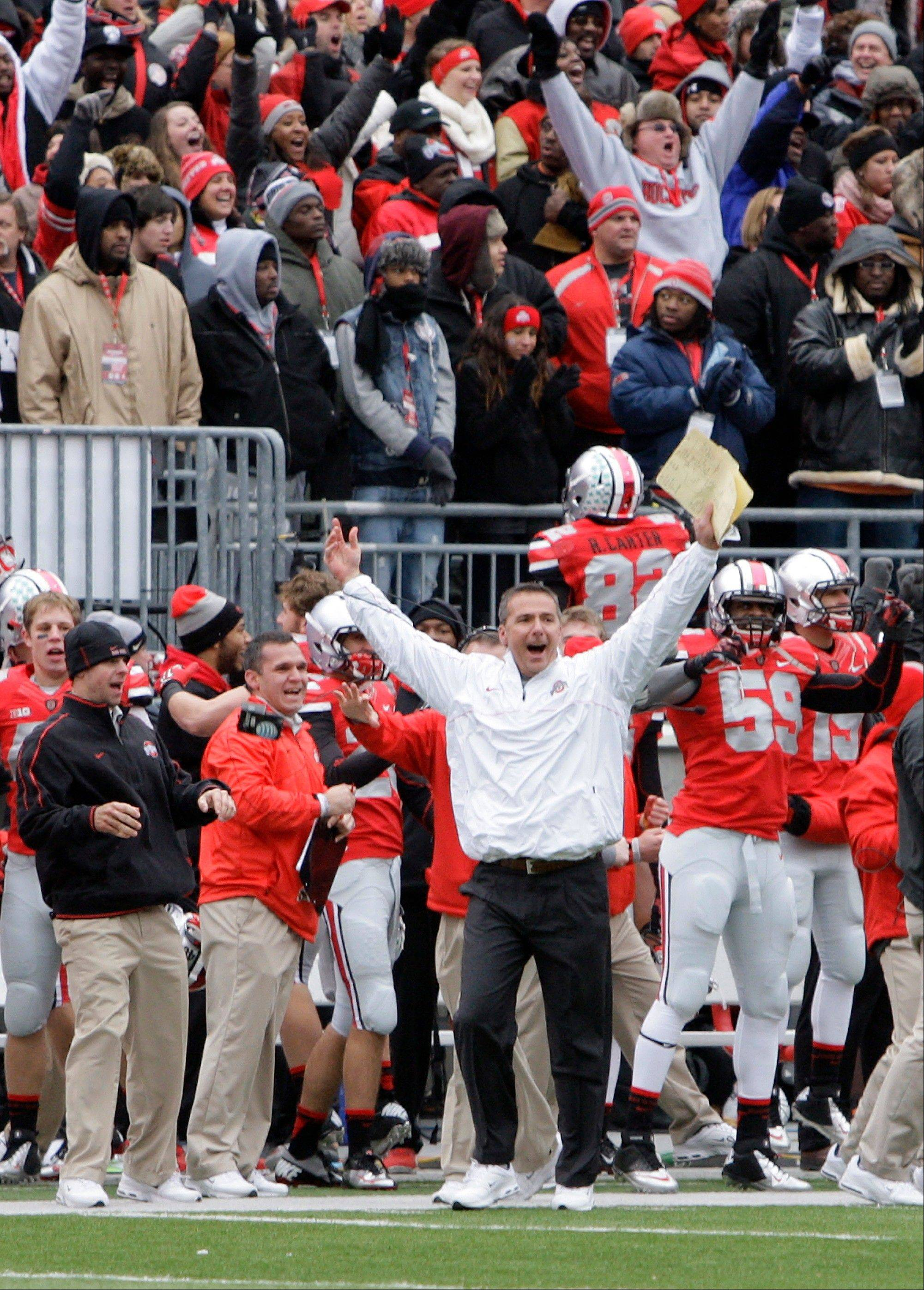 Ohio State head coach Urban Meyer celebrates as time runs off the clock in the Buckeyes� 26-21 home win over Michigan on Saturday. Ohio State went 12-0 this season but can�t play in a bowl game.