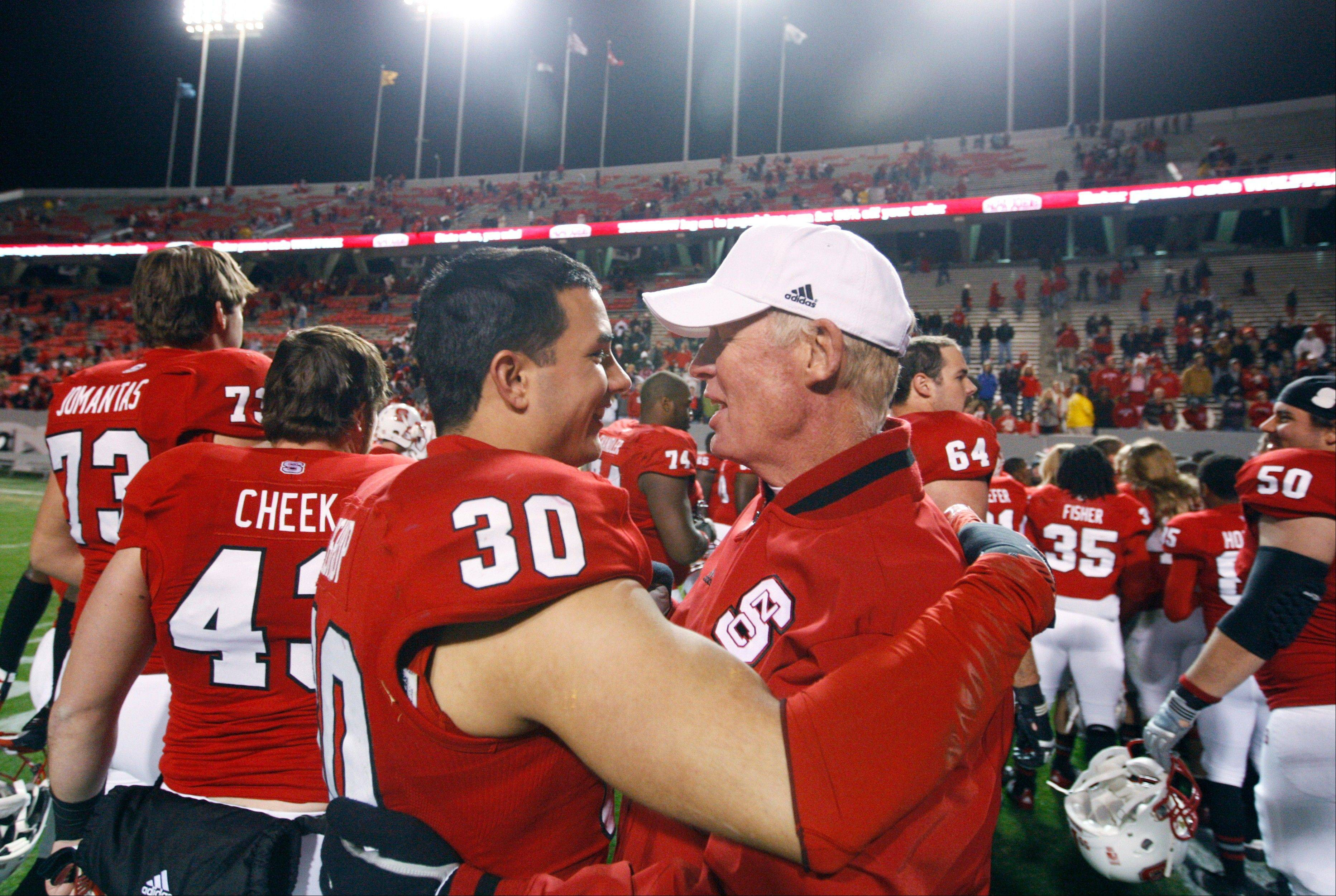 North Carolina State coach Tom O�Brien hugs senior Brandan Bishop after the team�s 27-10 victory over Boston College on Saturday. O�Brien was fired Sunday.