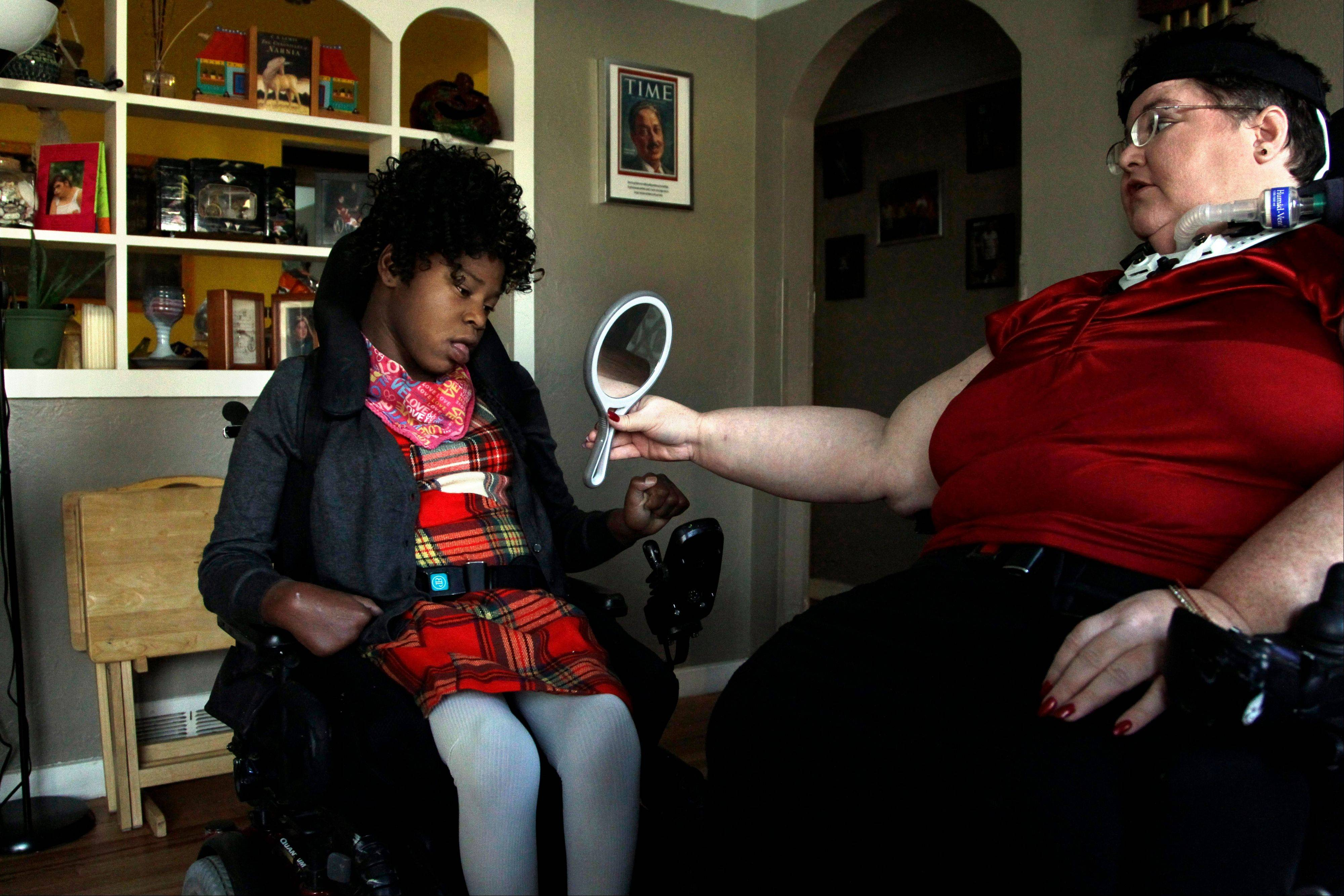 Carrie Ann Lucas, right, mother of four disabled adopted children, holds up a mirror for her daughter Adrianne, 13, at their home in Windsor, Colo., before going on an outing. Lucas herself uses a power wheelchair and is reliant on a ventilator due to a form of muscular dystrophy.