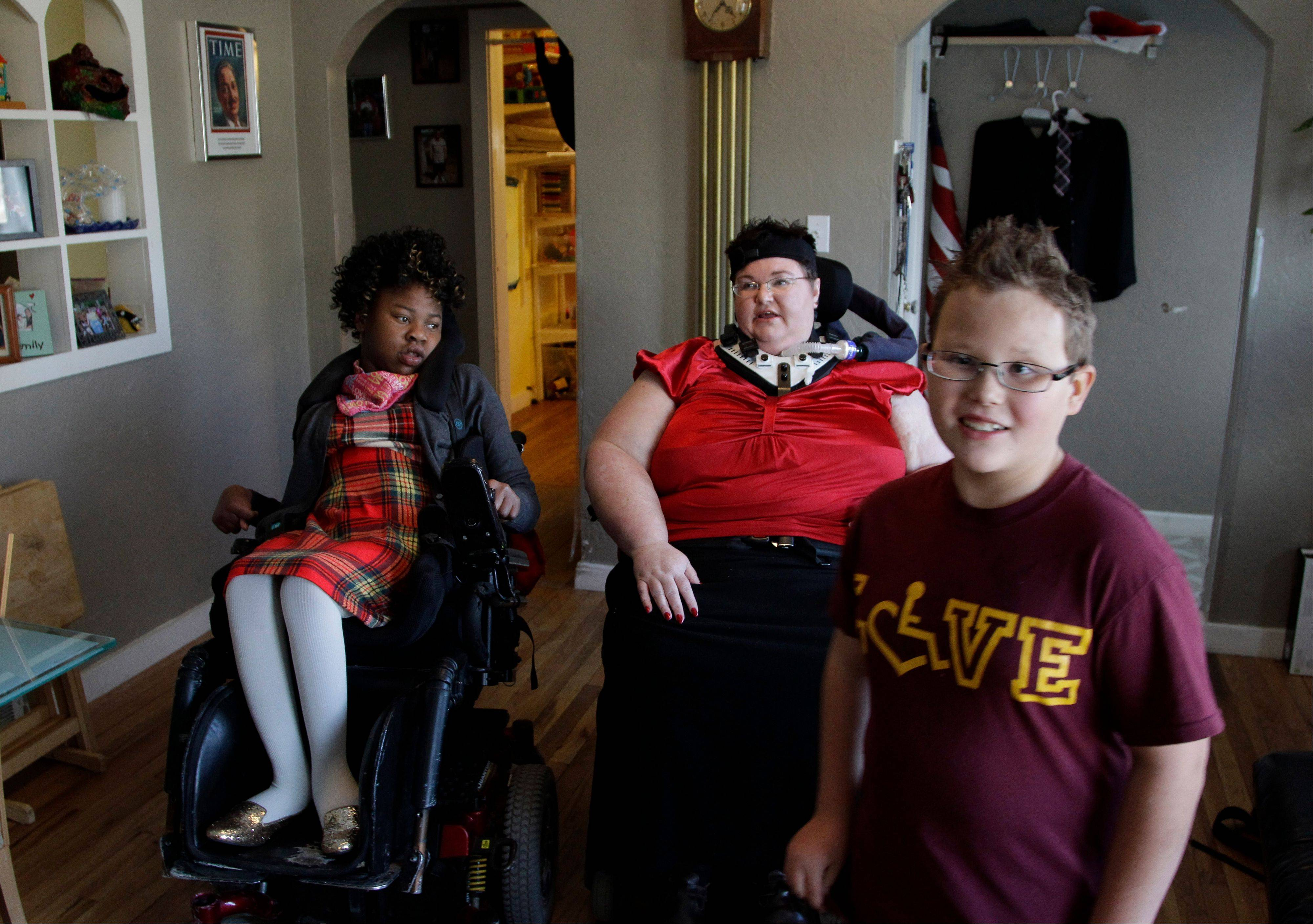 Carrie Ann Lucas, center, sits with her adopted daughter Adrianne, 13, as her adopted son Anthony, 11, walks past them as he gets himself ready in the morning at their home in Windsor, Colo.