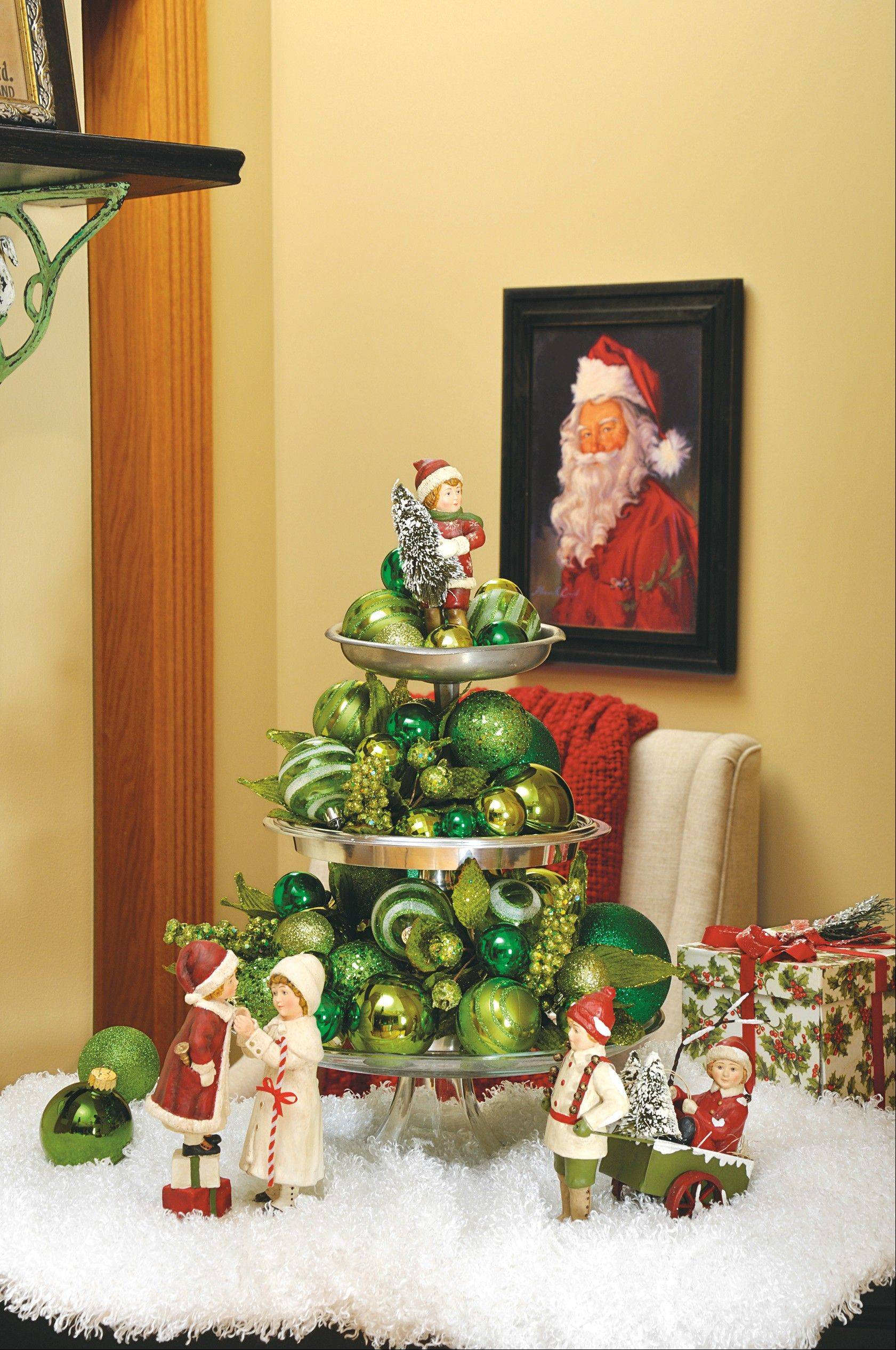 "A glass cake plate, topped with a footed compote and an antique candy dish sets the structure for this ""tree"" filled wiht solid and crackled green ornaments in green of various shades."