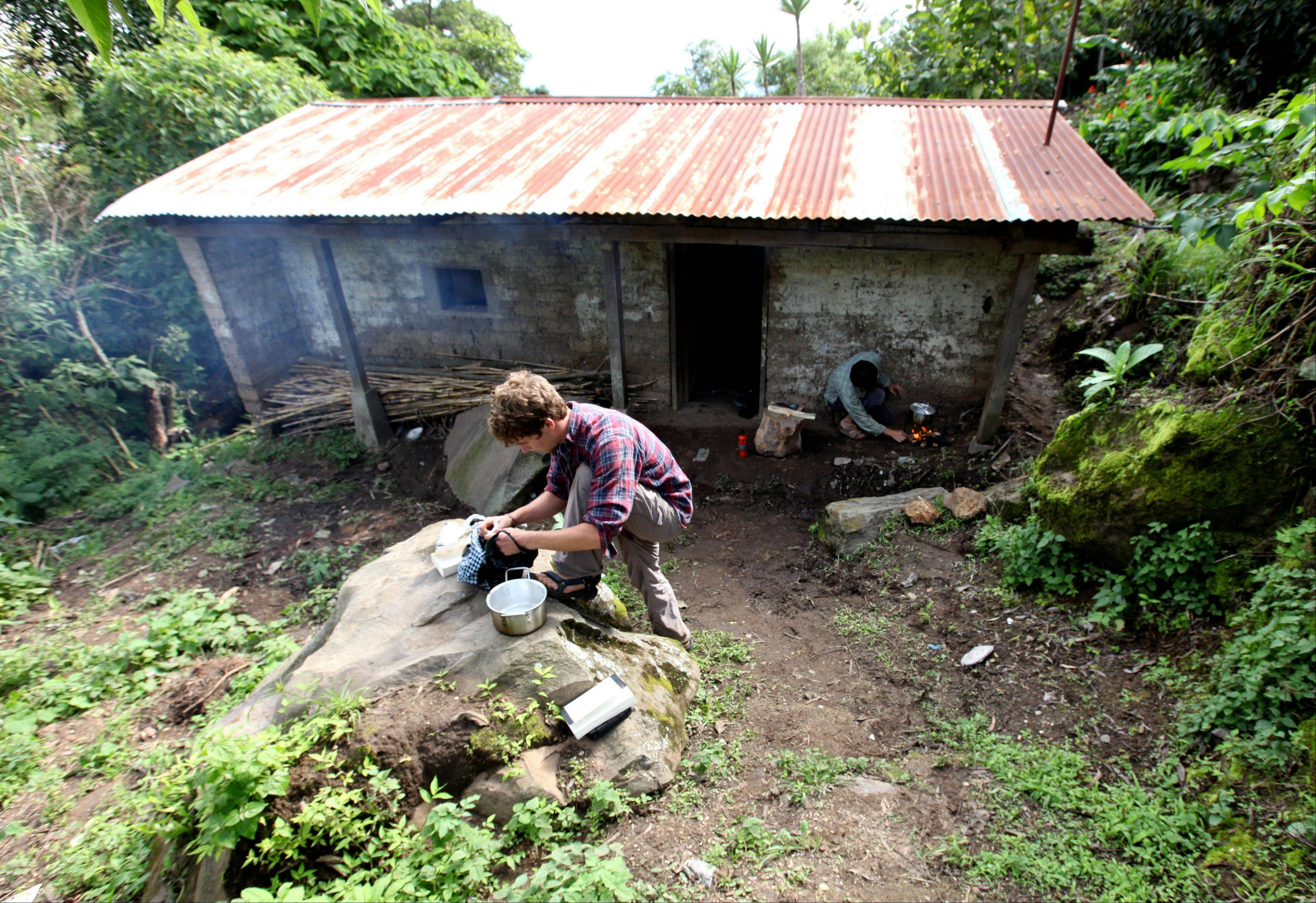 Chris Temple and Ryan Christofferson prepare food outside the dirt-floor hut where they lived for a summer in the village of Pena Blanca, Guatemala.