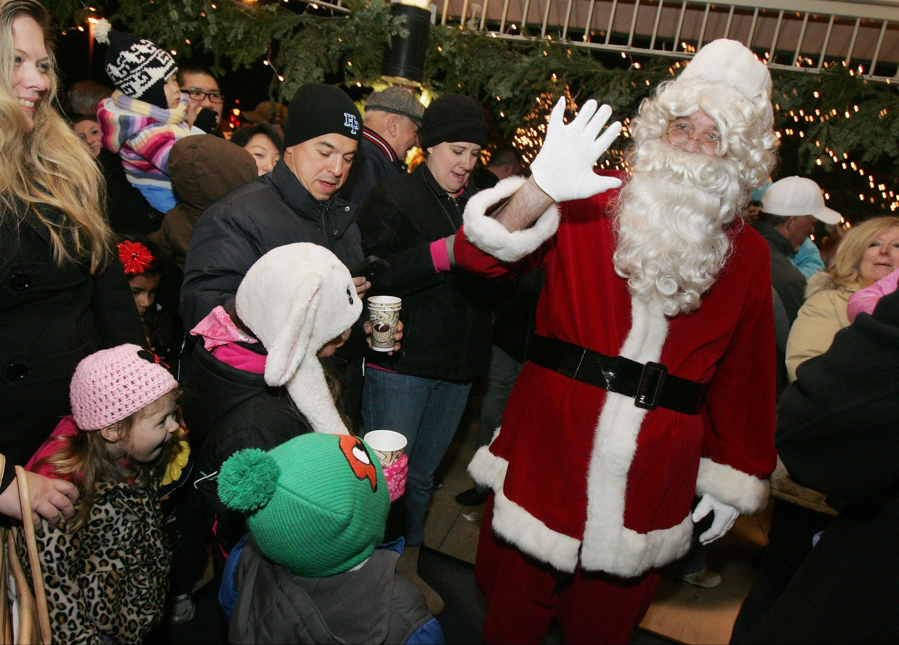 Santa Claus arrives and greets children during Wheeling's Lighting of the Lights Sunday at Friendship Park. Holiday music was performed by Wheeling High School band members and hot chocolate and cookies were provided by Market Square Restaurant.