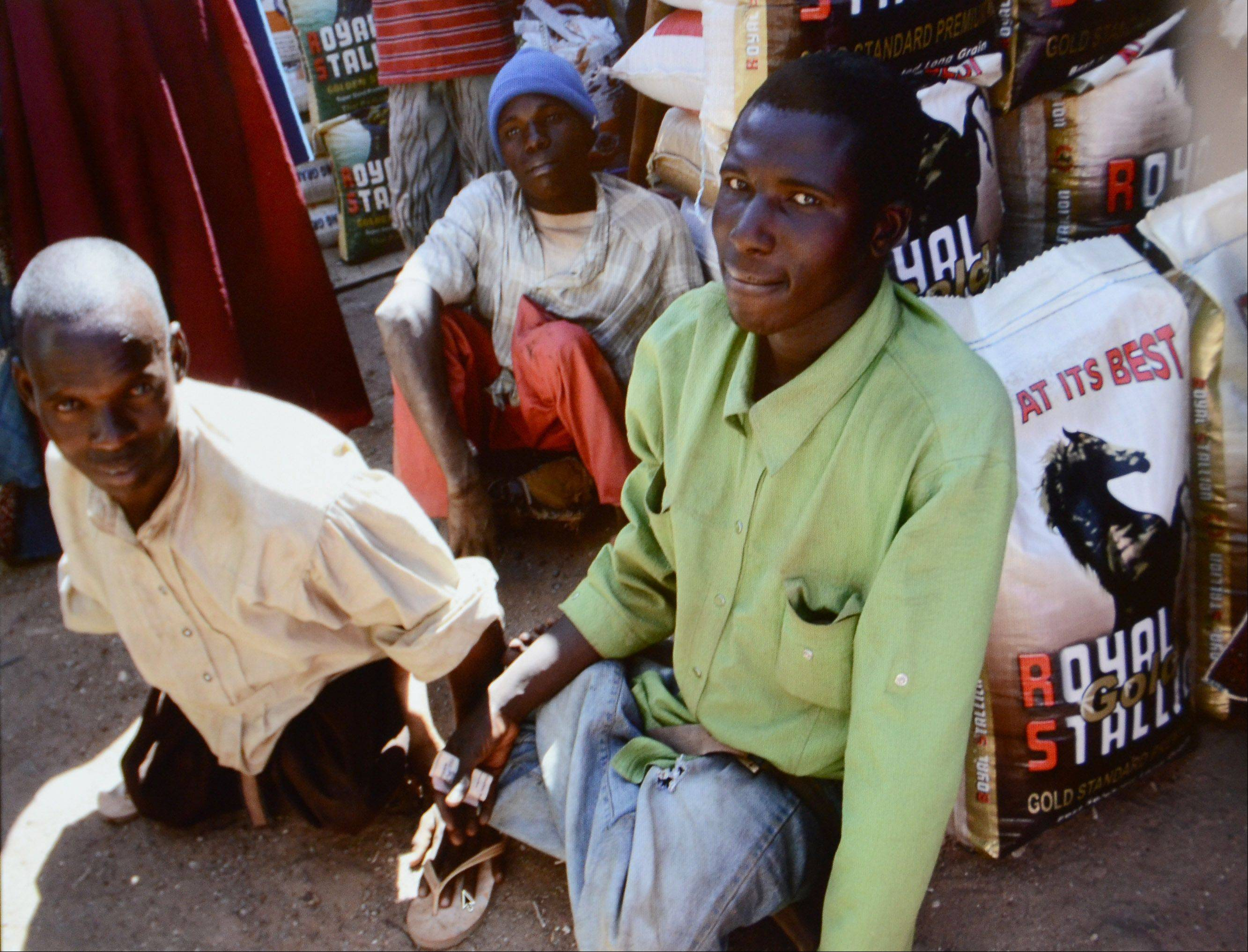 Polio survivors sit on the ground in a market in Nigeria.