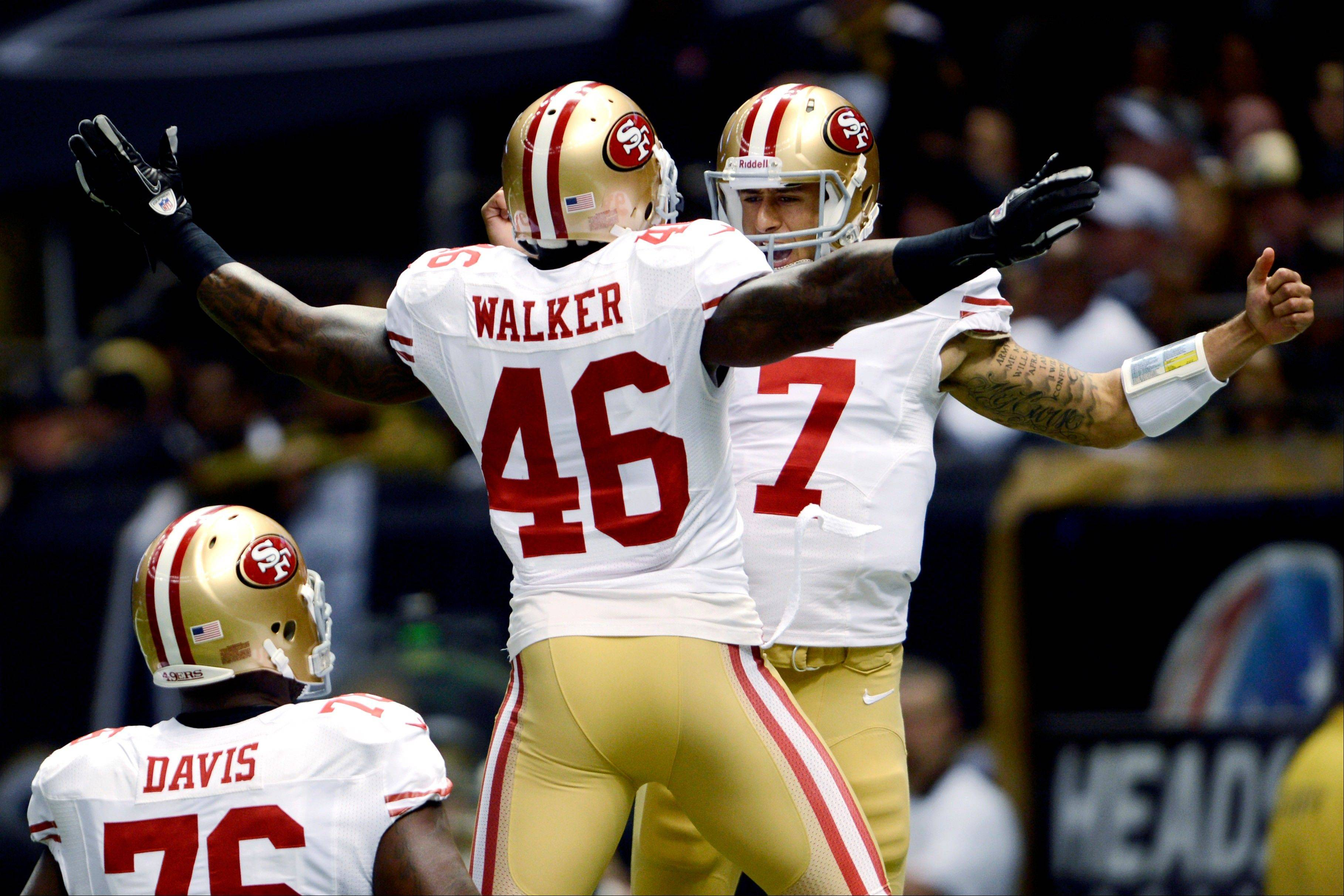 San Francisco 49ers quarterback Colin Kaepernick (7) celebrates his rushing touchdown with tight end Delanie Walker (46) in the first half against the New Orleans Saints in New Orleans, Sunday. The 49ers won 31-21.