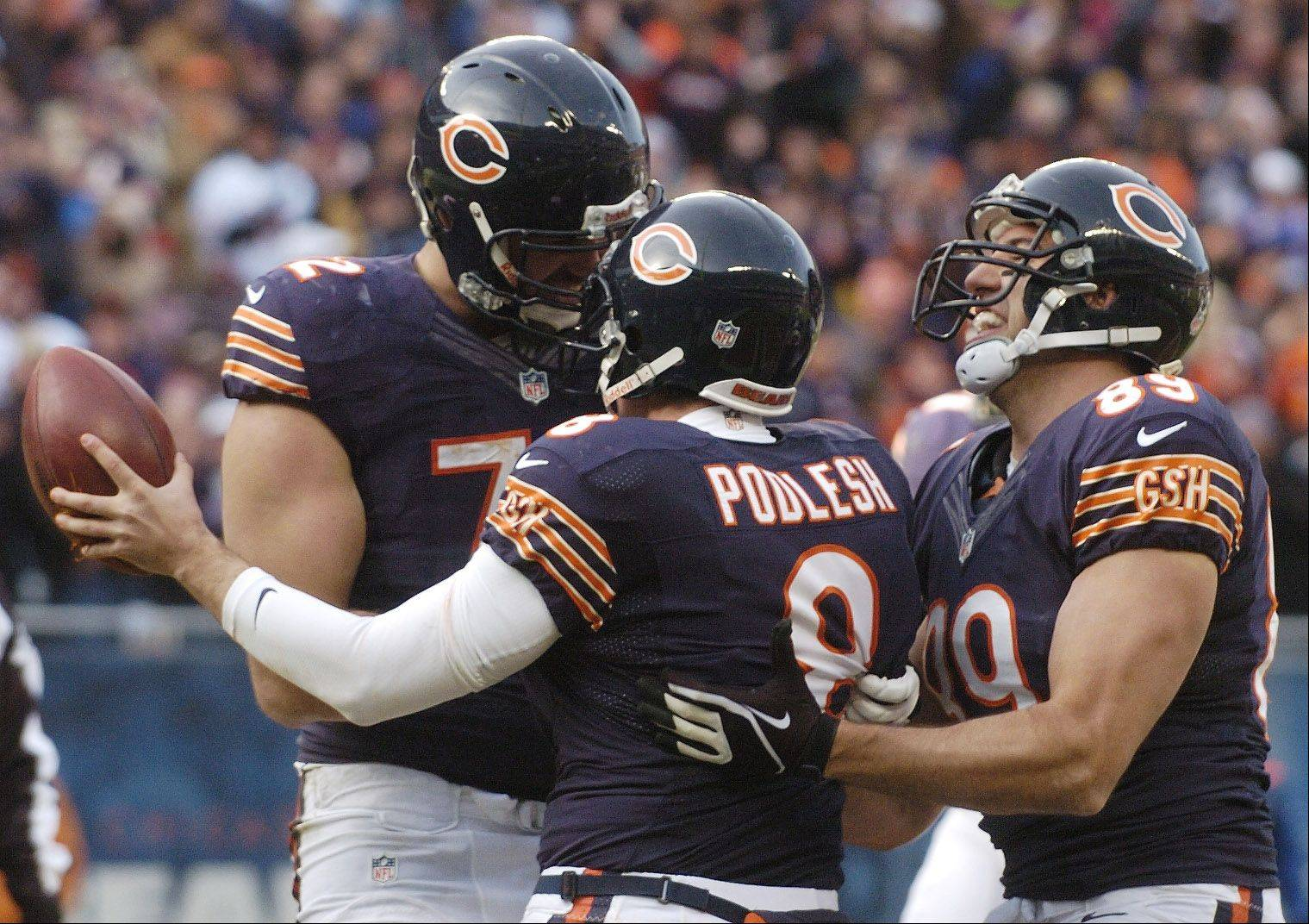 Chicago Bears holder Adam Podlesh, middle, celebrates his two-point conversion with teammates Gabe Carimi, left, and Matt Spaeth during the second quarter at Soldier Field Sunday.