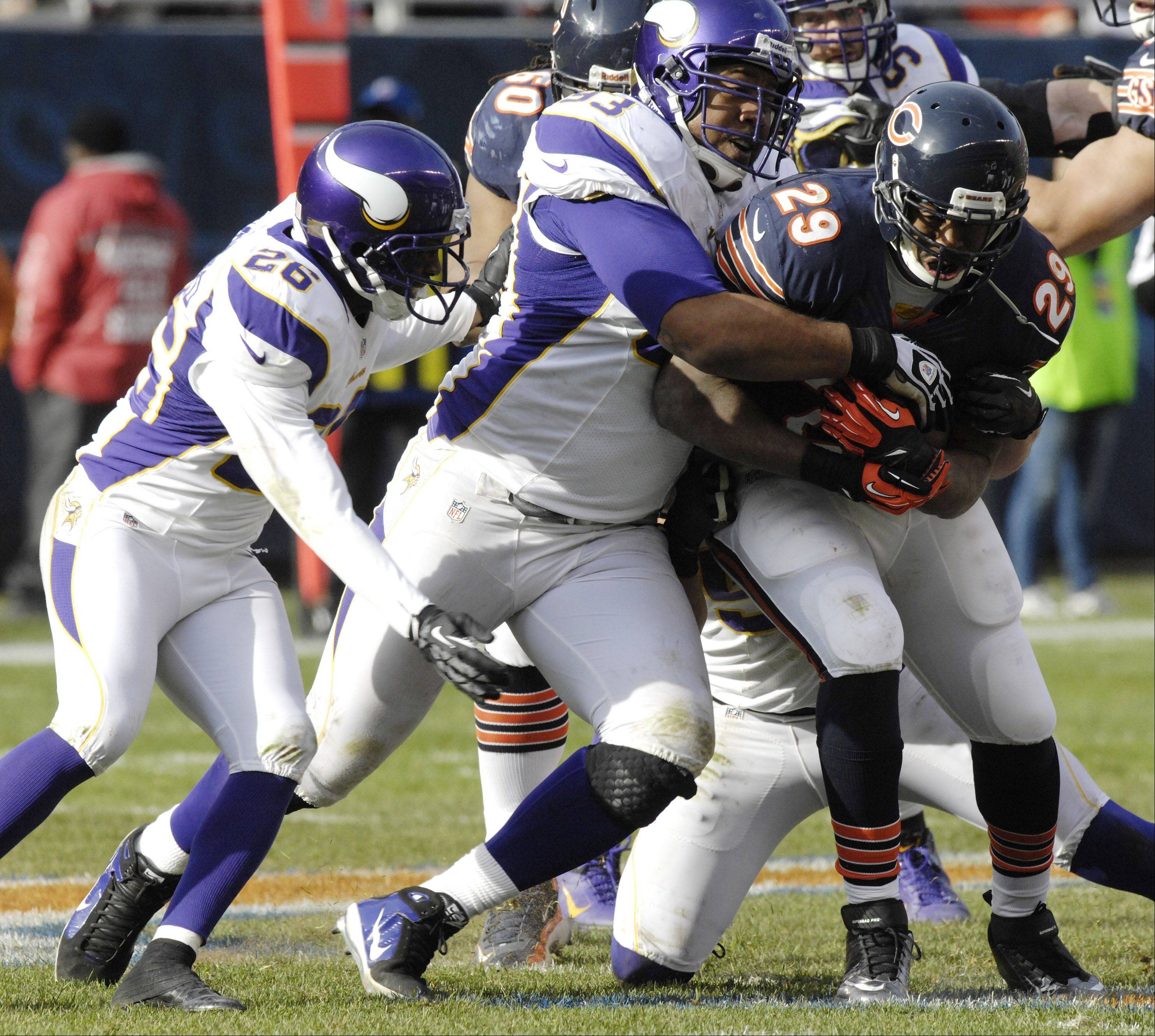 Chicago Bears running back Michael Bush gets tackled by Minnesota Vikings defensive tackle Kevin Williams, middle, and cornerback Antoine Winfield at Soldier Field Sunday.