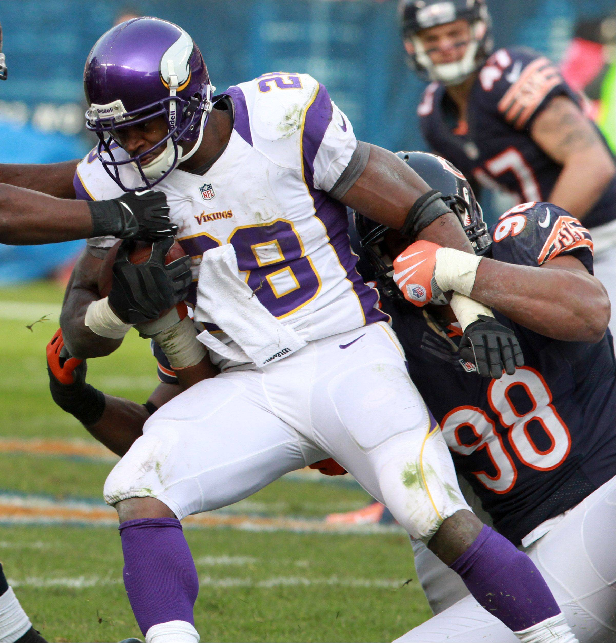 Vikings running back Adrian Peterson is dragged down by Bears defensive end Corey Wootton at Soldier Field Sunday.