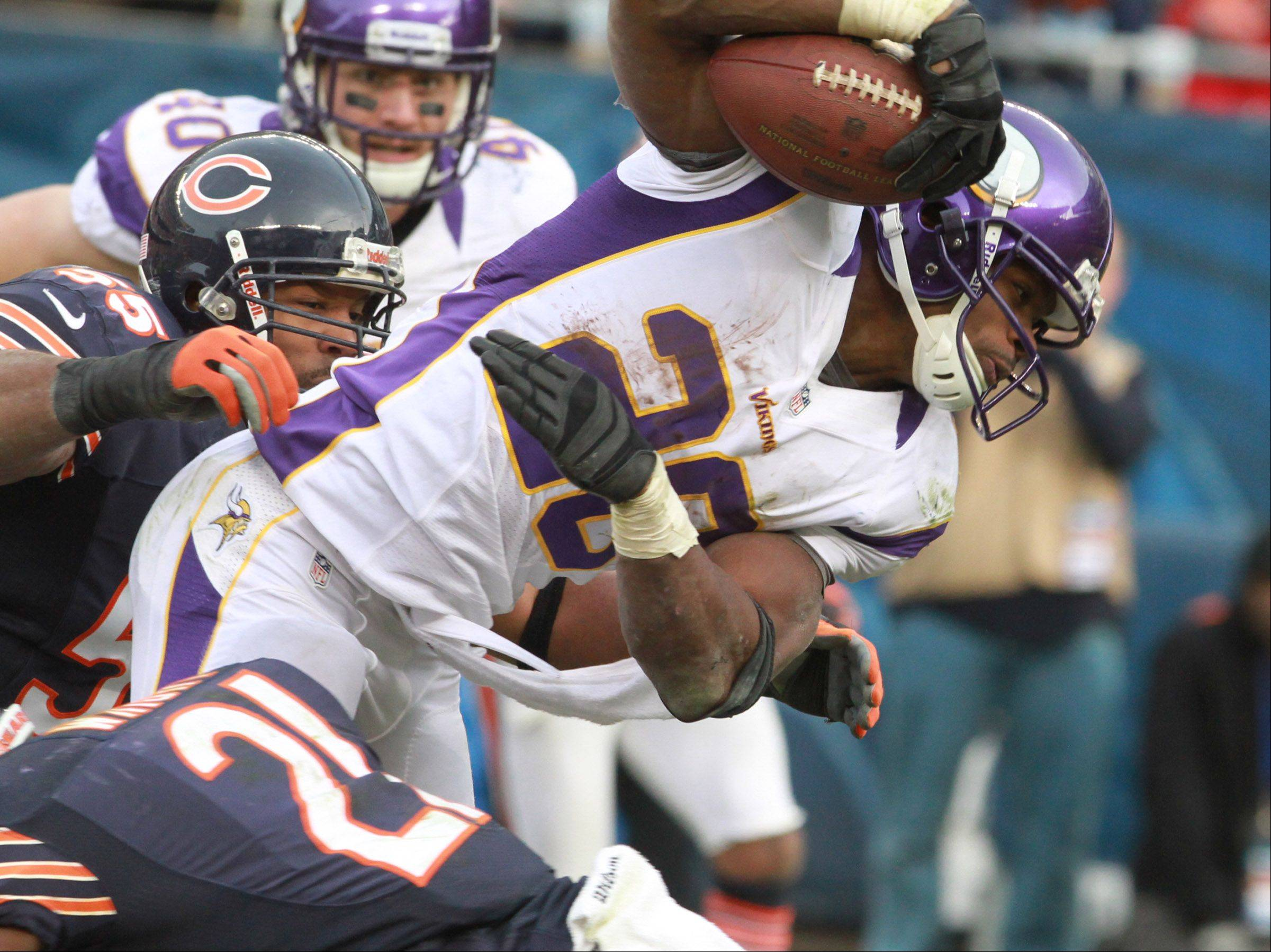 Minnesota Vikings running back Adrian Peterson is tripped up by Chicago Bears strong safety Major Wright, lower left, at Soldier Field Sunday.