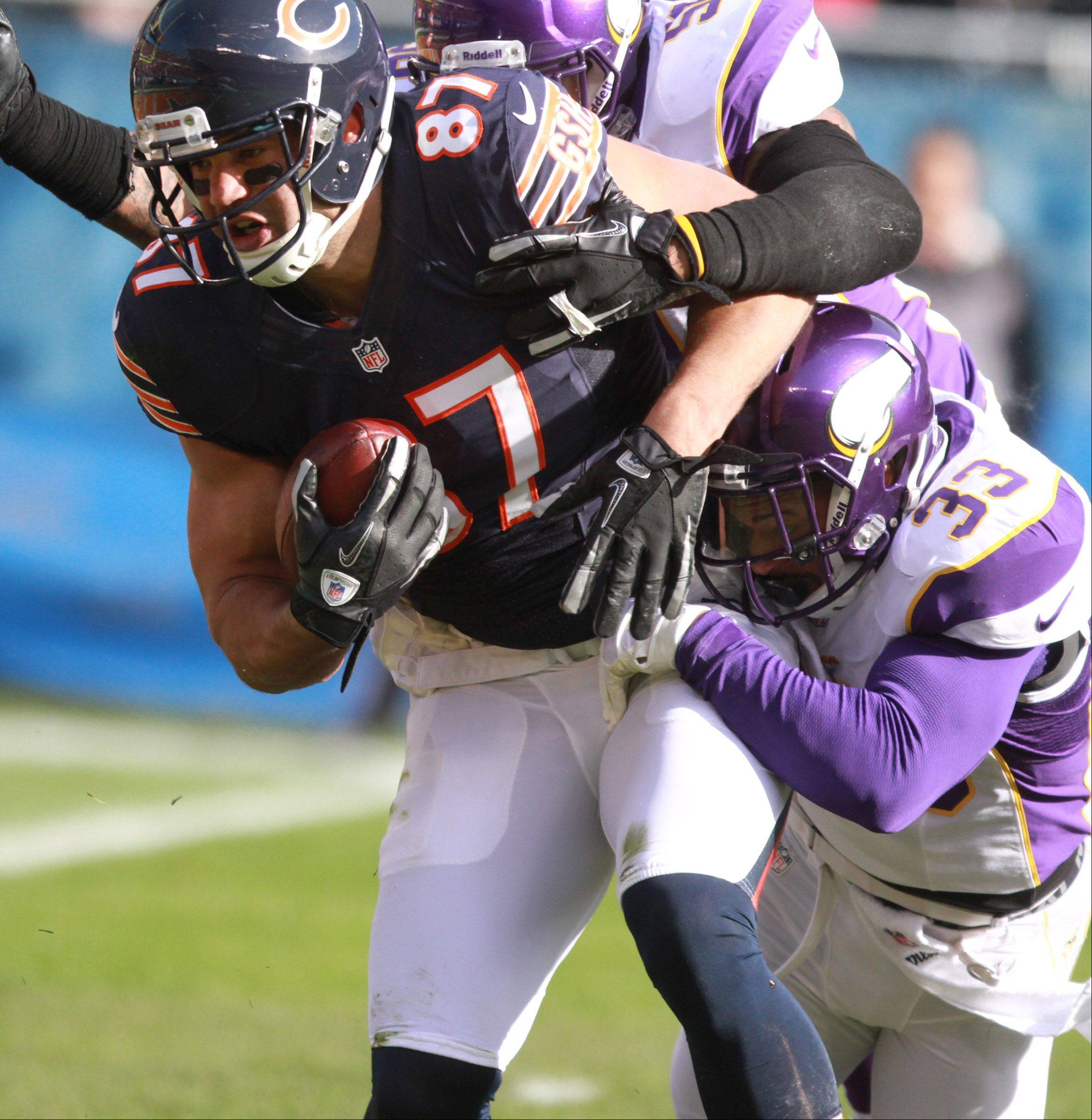 Chicago Bears tight end Kellen Davis is dragged down by Minnesota Vikings strong safety Jamarca Sanford at Soldier Field Sunday.