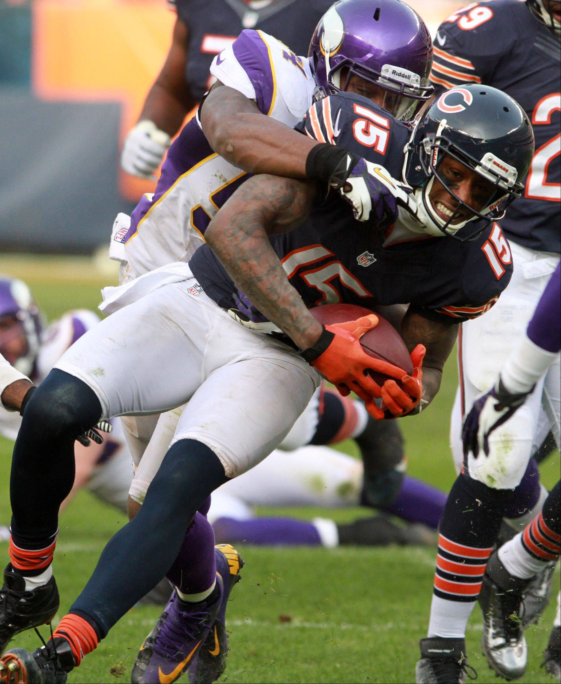 Chicago Bears Brandon Marshall is dragged down by Minnesota Vikings' Jasper Brinkley after catching a pass from quarterback Jay Cutler at Soldier Field Sunday.