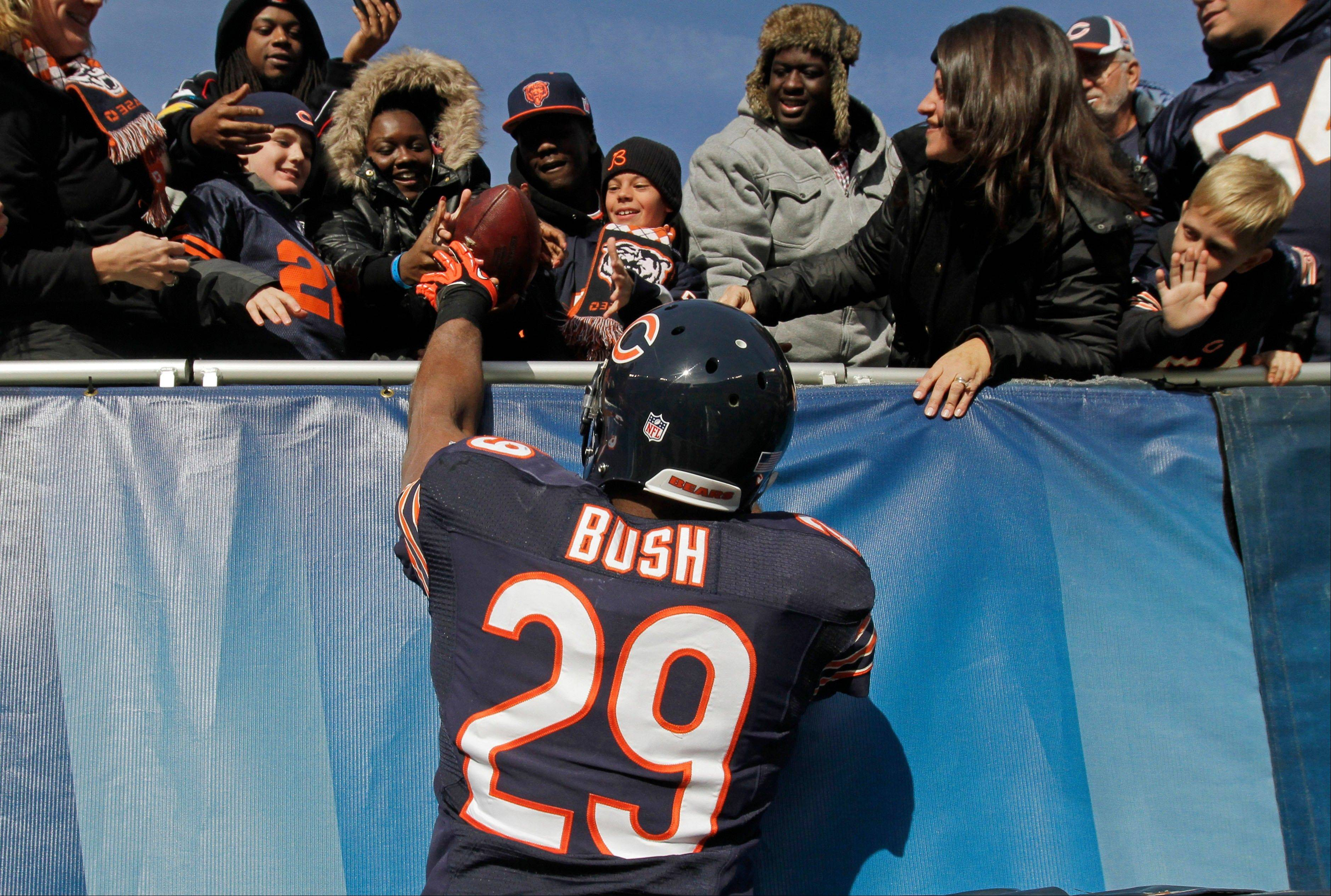 Chicago Bears running back Michael Bush (29) gives a ball to a fan after making a touchdown run in the first half of an NFL football game against the Minnesota Vikings in Chicago, Sunday.