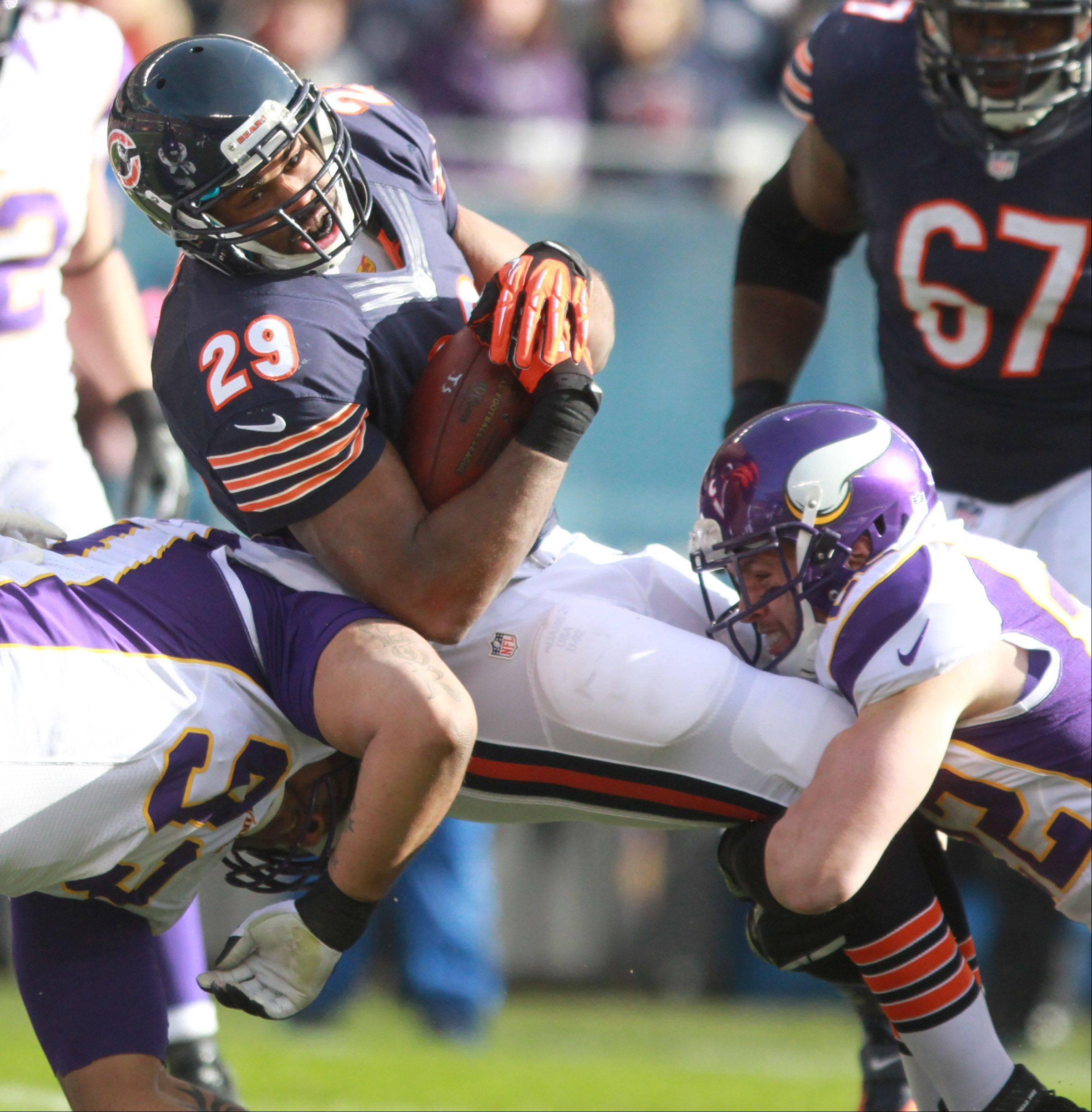 Chicago Bears running back Michael Bush is pulled down by Vikings free safety Harrison Smith and defensive tackle Kevin Williams at Soldier Field Sunday.
