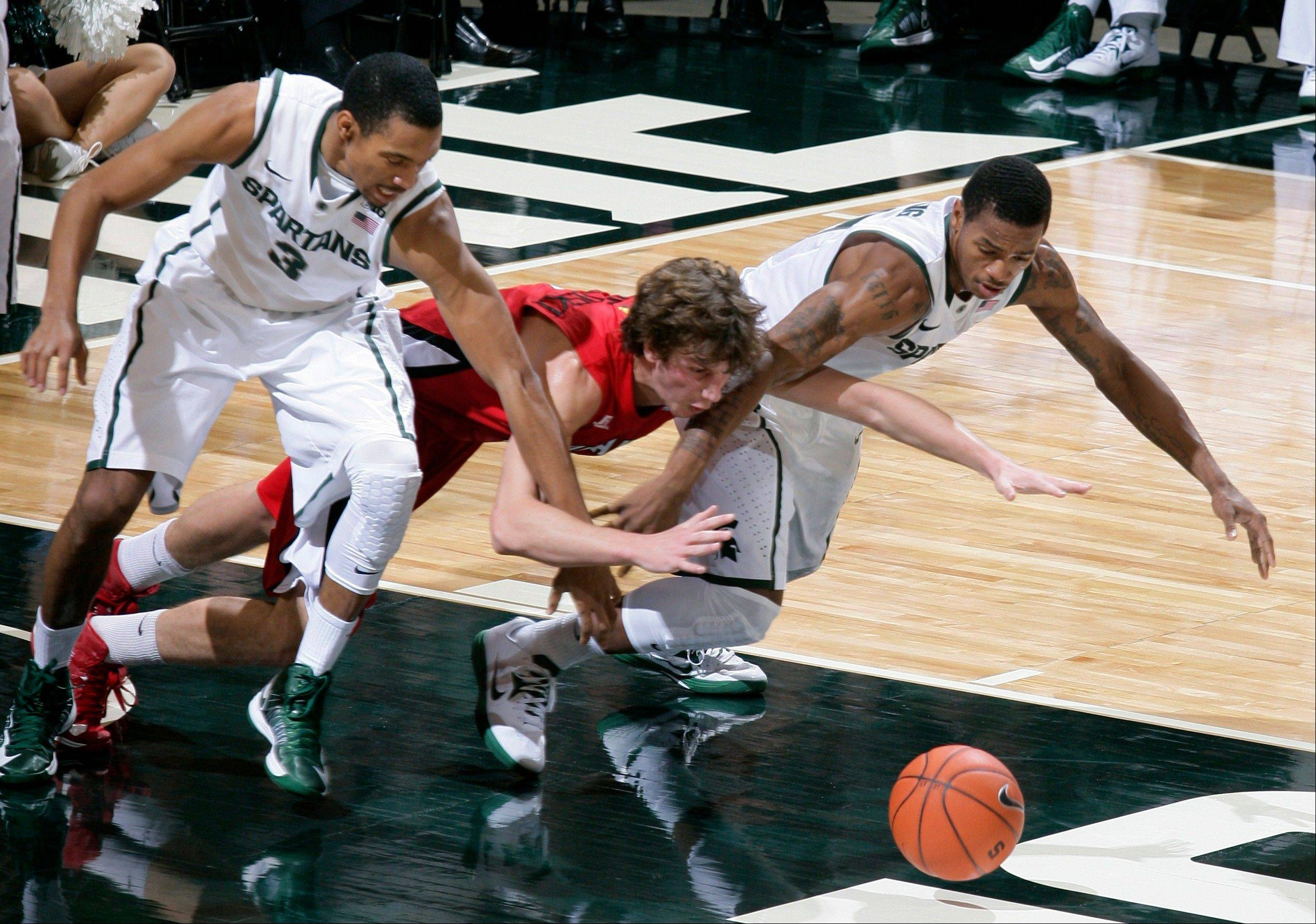 Michigan State's Brandan Kearney, left, Louisiana Lafayette's Steven Wronkoski, center, and Michigan State's Keith Appling dive for a loose ball during the first half of Sunday's game in East Lansing, Mich.