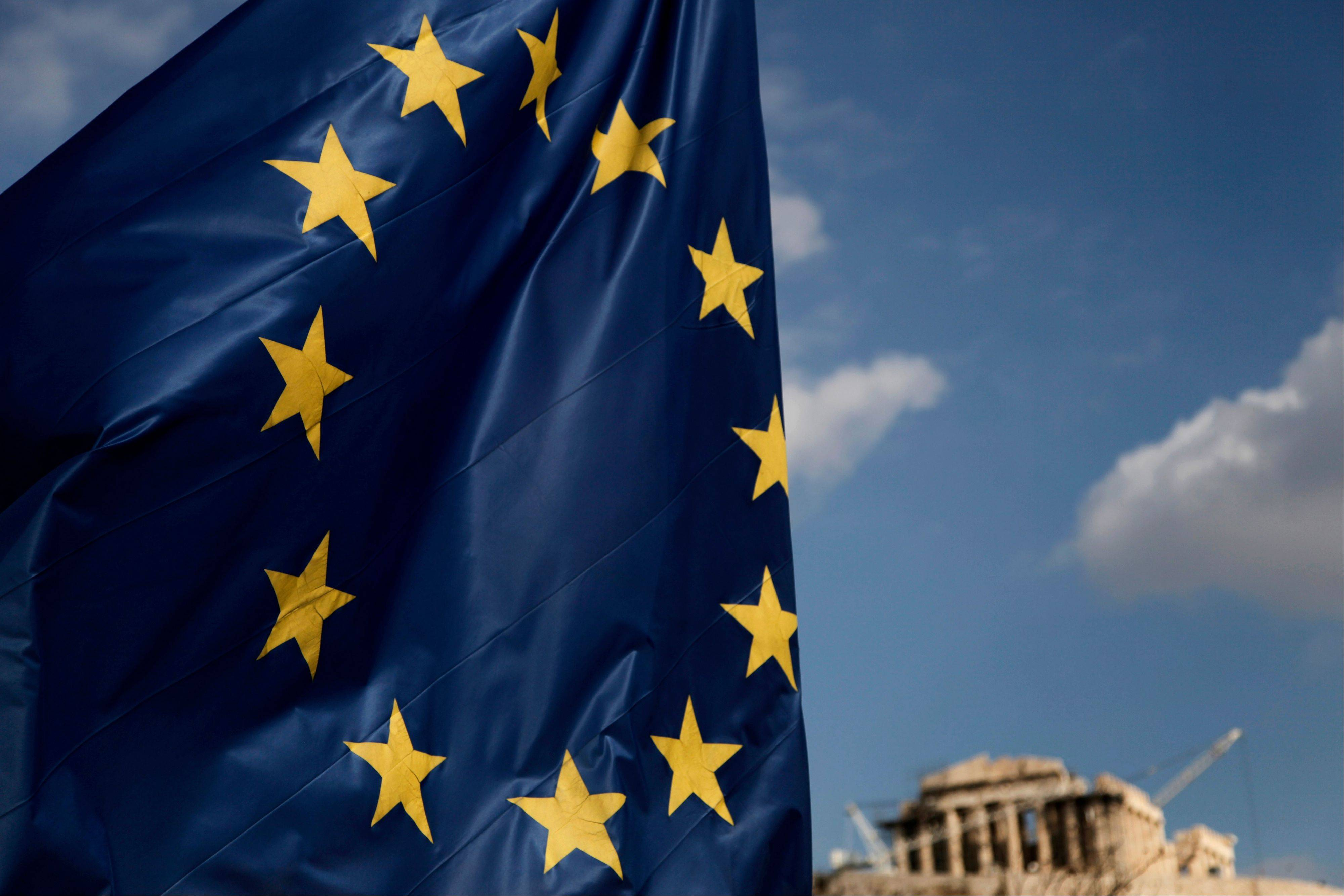 A European Union flag billows in the wind as the Parthenon temple is seen in the background on the Acropolis in Athens Monday. The ministers of the 17 countries that use the euro met in Brussels Monday to settle on Greece�s next rescue loan installment.