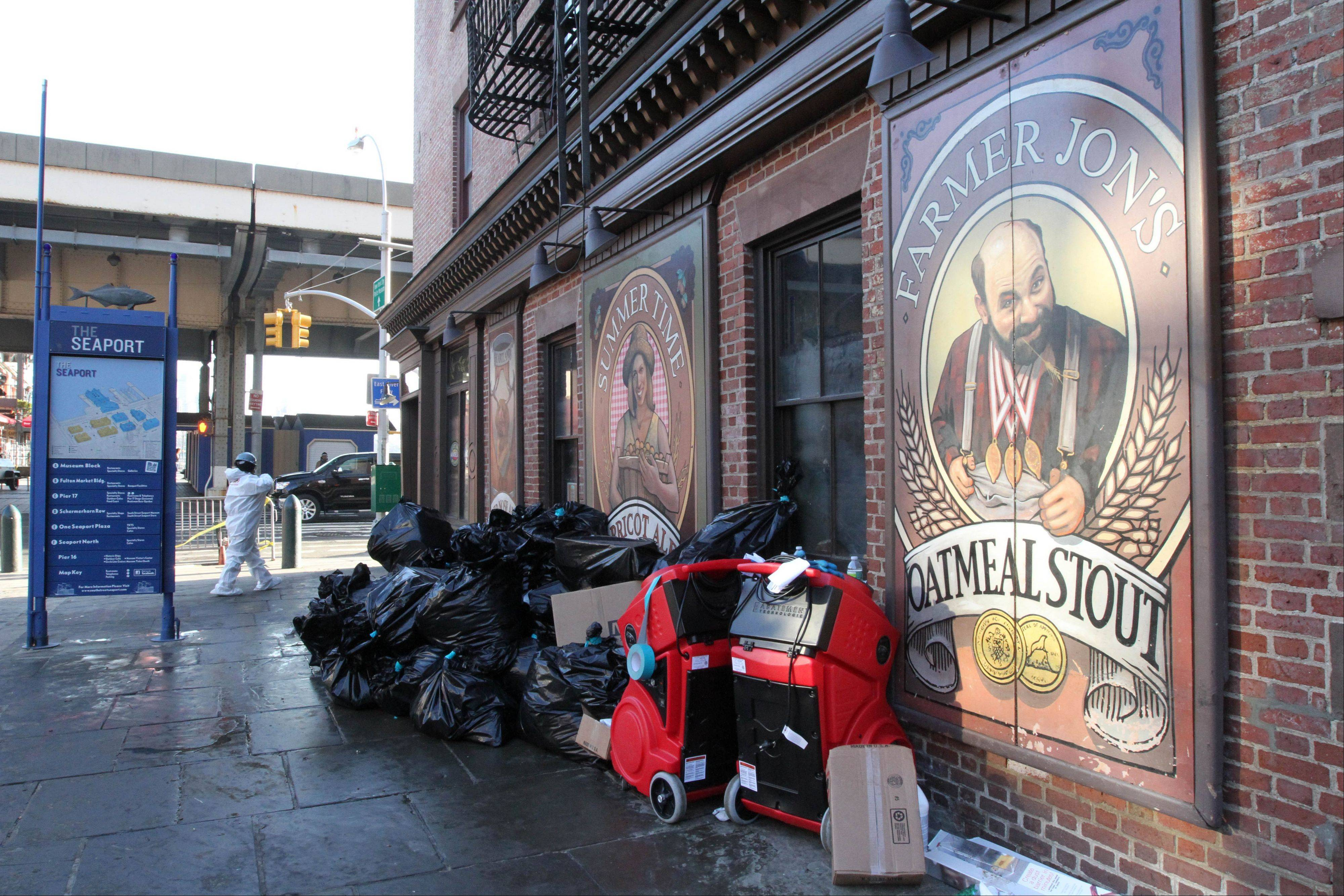 A worker wearing protective clothing enters the Heartland Brewery at New York�s South Street Seaport, as bags of garbage from the Superstorm Sandy cleanup sit out front.