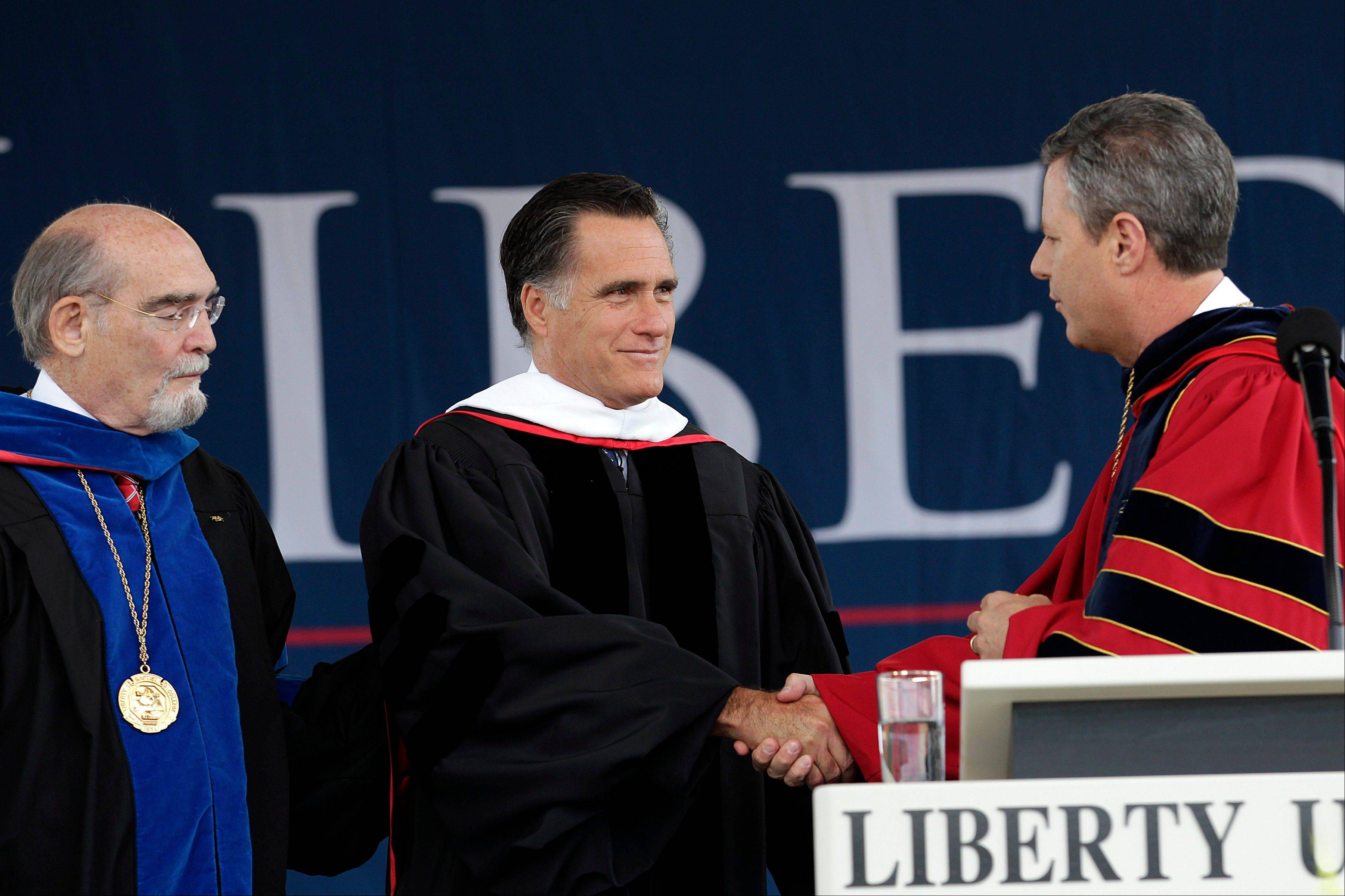 The U.S. Supreme Court has given new life to Liberty University�s challenge to President Barack Obama�s healthcare overhaul. Republican presidential candidate, former Massachusetts Gov. Mitt Romney, center, is seen here shaking hands with Jerry Falwell Jr., chancellor of Liberty University, before his commencement speech at the campus in Lynchburg, Va., May 12, 2012.
