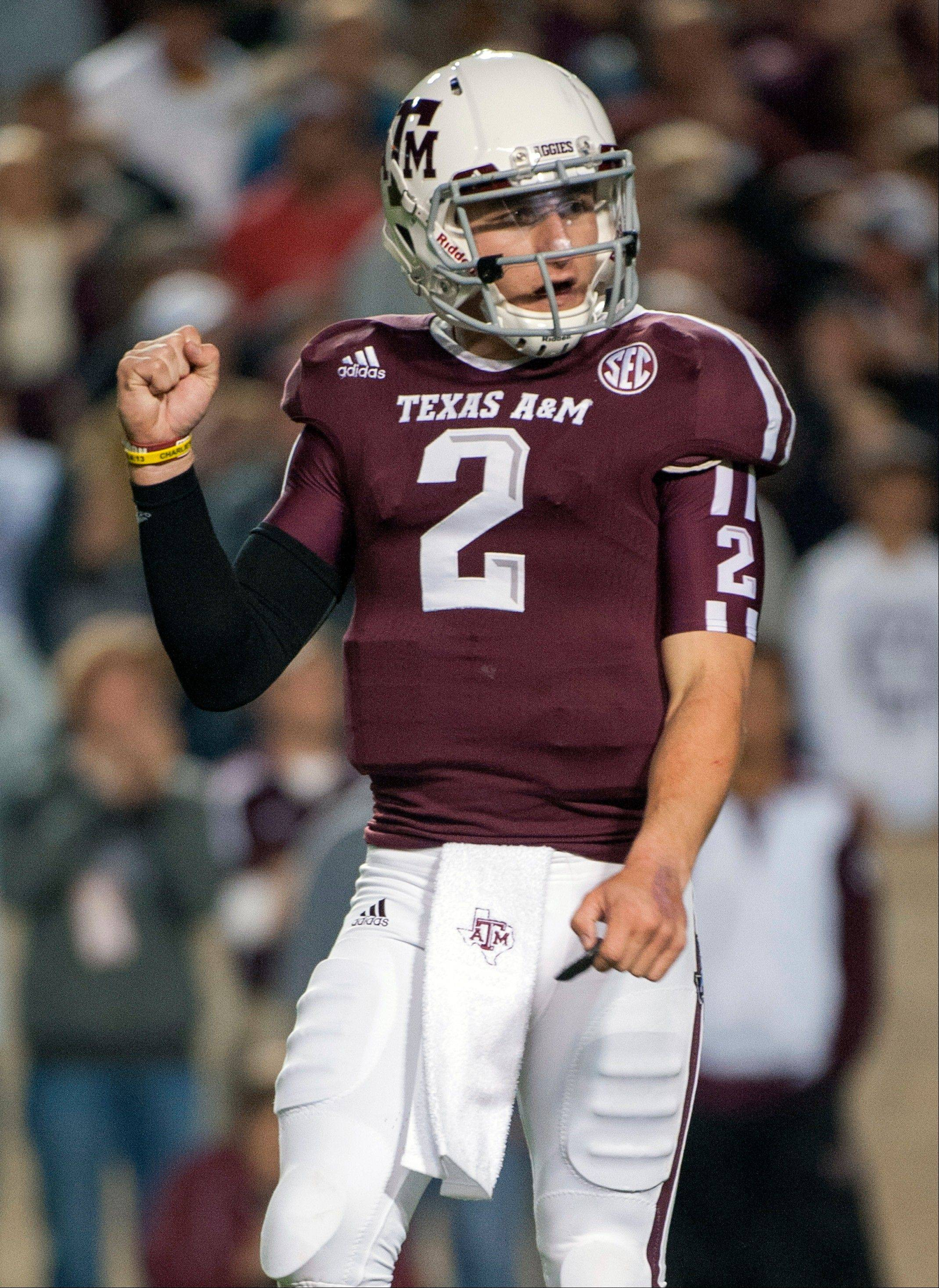 Texas A&M quarterback Johnny Manziel reacts after a touchdown run by teammate Ben Malena during the first quarter an NCAA college football game against Missouri, Saturday, Nov. 24, 2012, in College Station, Texas. Manziel, aka Johnny Football, spoke to the media for the first time this season.