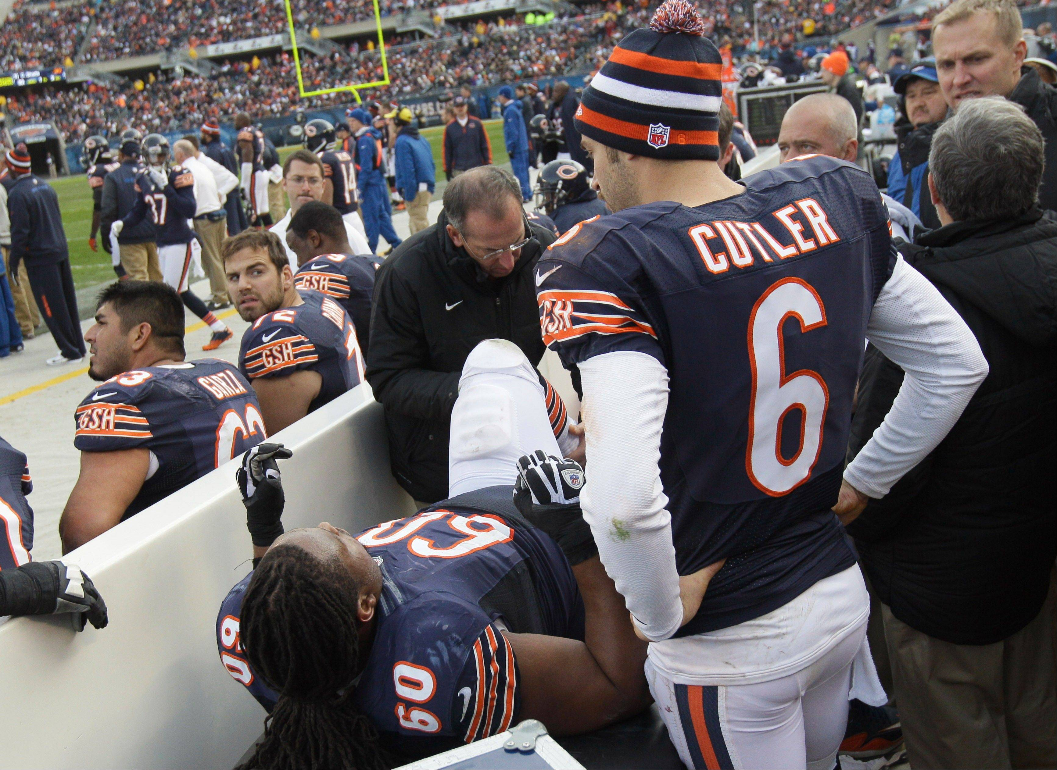 Bears quarterback Jay Cutler looks on as a trainer examines the left leg of injured guard Lance Louis in Sunday�s game against the Minnesota Vikings at Soldier Field. Louis is out for the season with a knee injury.