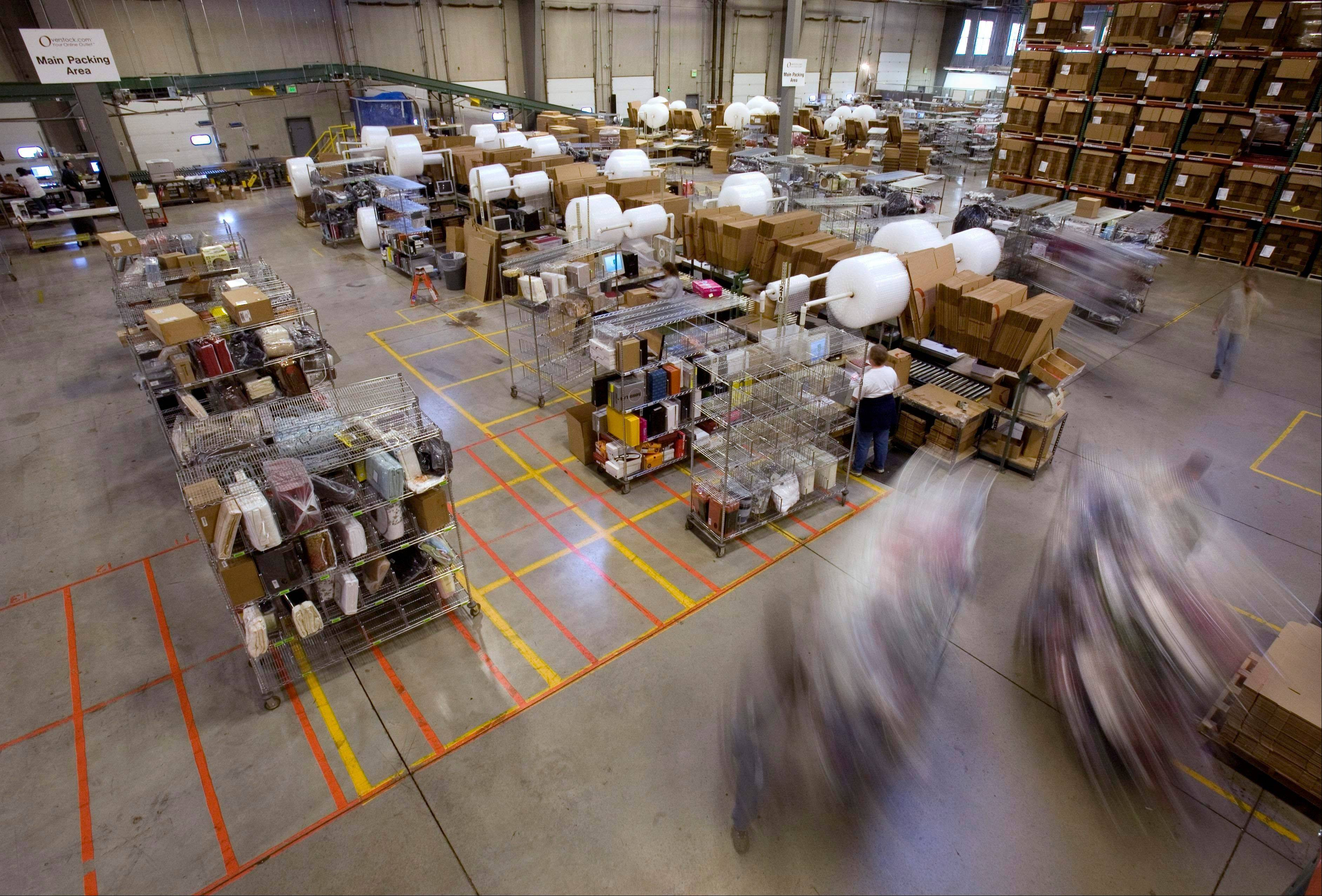 Carts full of merchandise ordered online are rolled to the main packing area for shipping at the Overstock.com warehouse, in Salt Lake City.