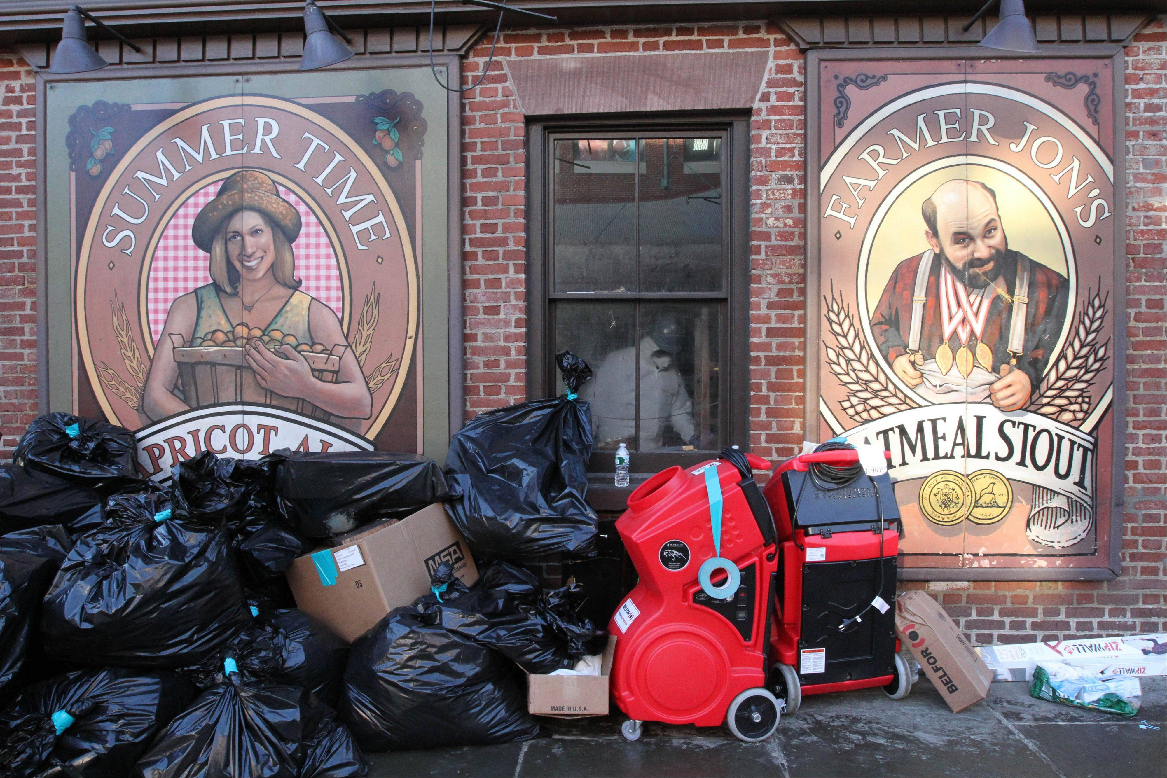 A worker wearing protective clothing, behind window, toils inside the Heartland Brewery at New York's South Street Seaport, as bags of garbage from the Superstorm Sandy cleanup sit out front. The South Street Seaport, a popular tourist destination, remains a ghost town since the storm.
