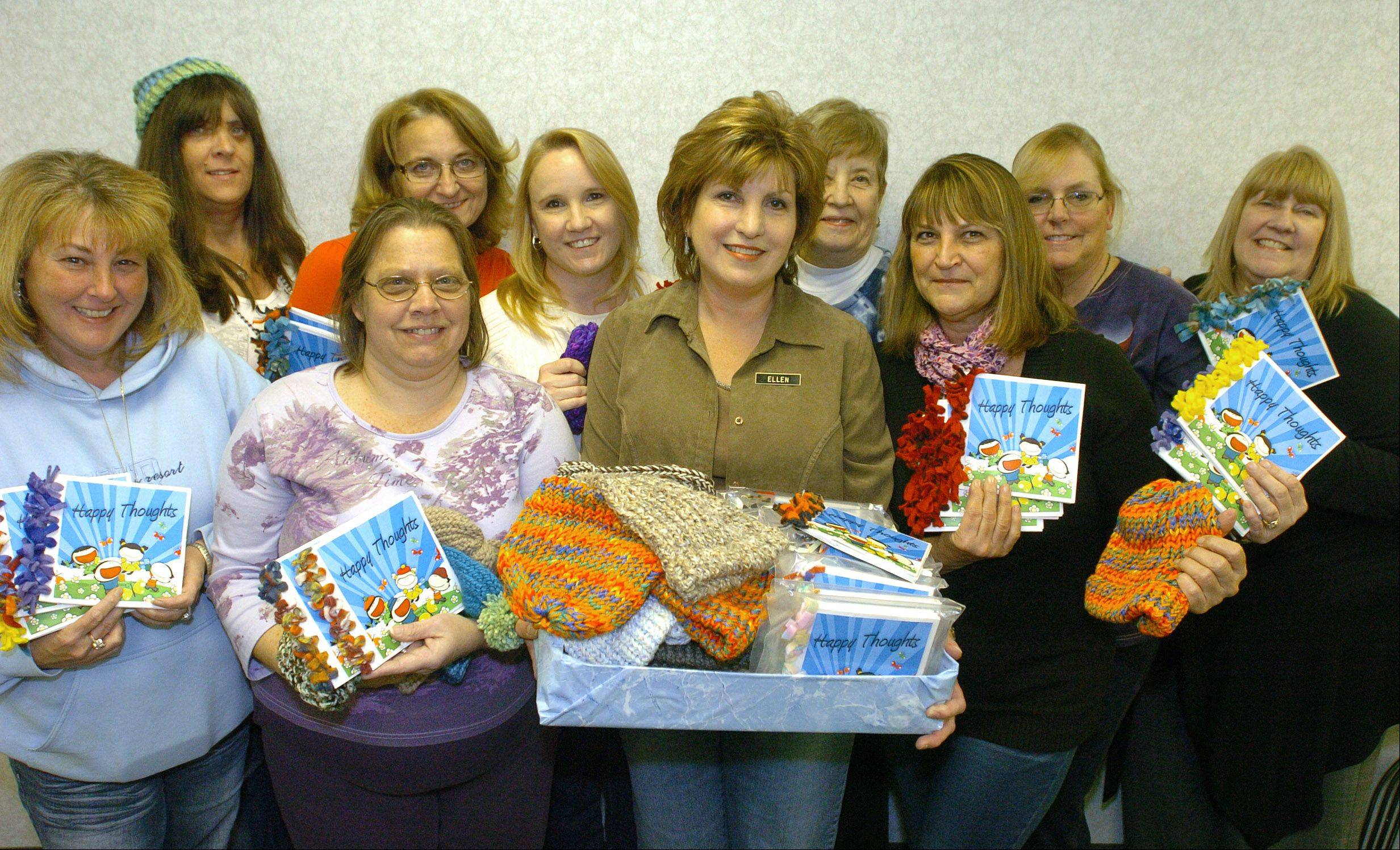 Happy Caps founder Ellen Hart, center, began recruiting this team of volunteers and others for her new organization earlier this year. The group knits caps for cancer patients and makes journals for them and behavioral health patients, too.