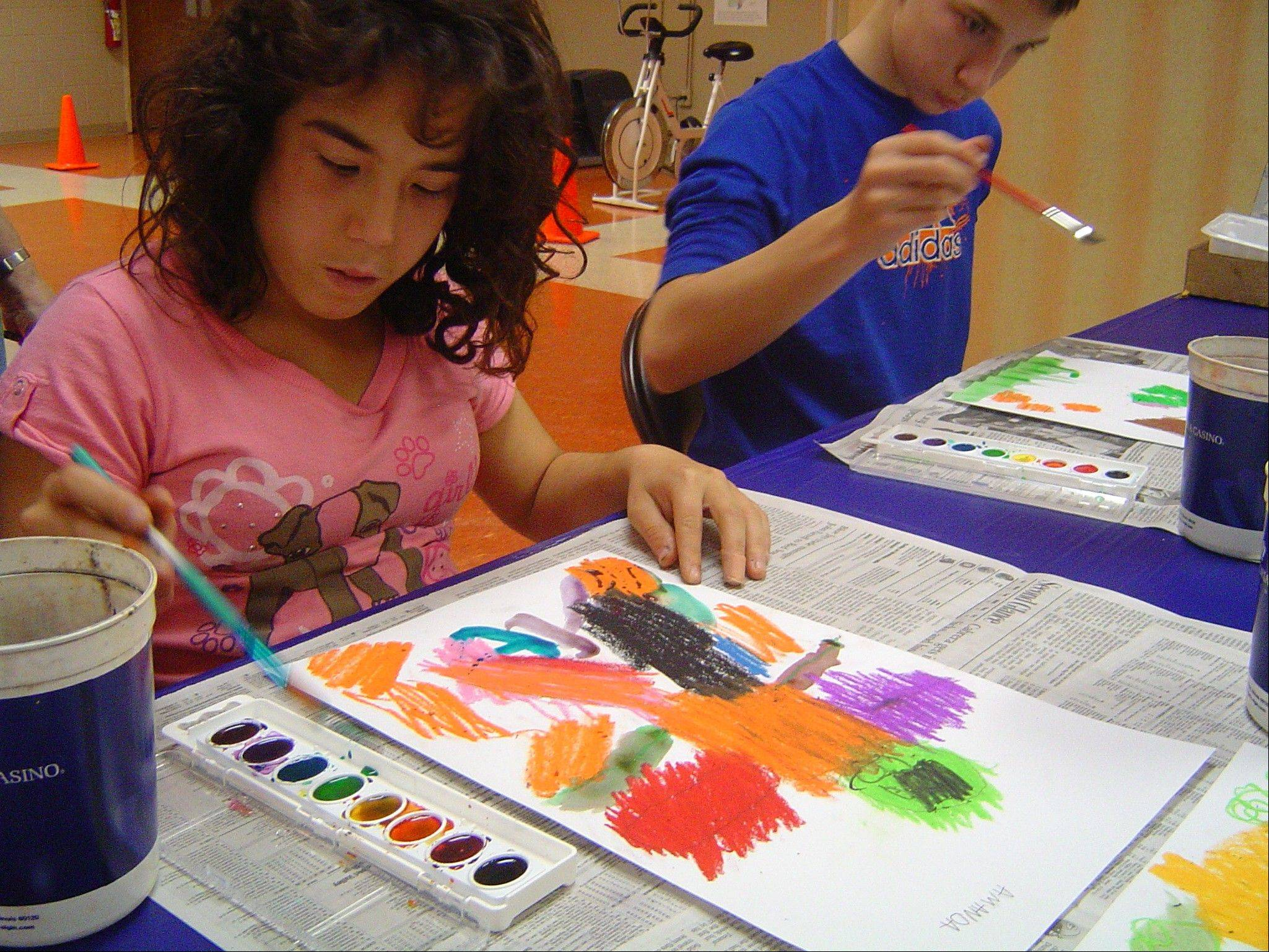 Amanda Lyubelsky, left, of Carol Stream and Tim Hayes of Wheaton paint scarecrows at a Tuesday art program.