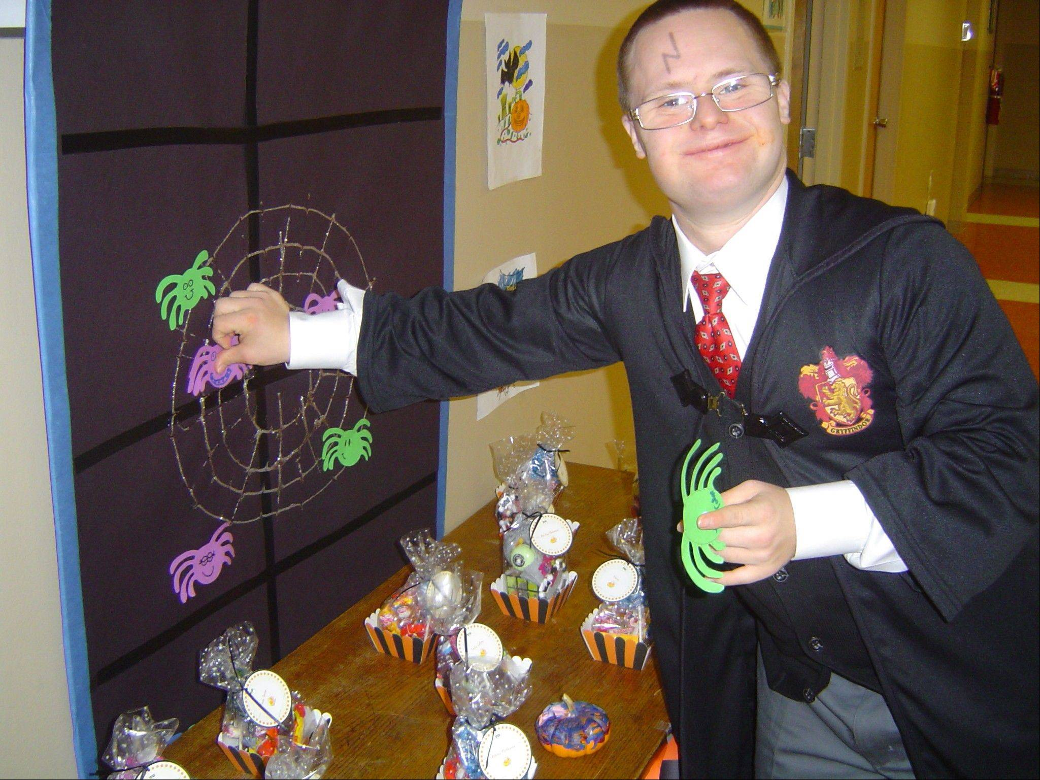 Sean Doran of Wheaton pins the spider on the web at a Saturday night social Halloween party.