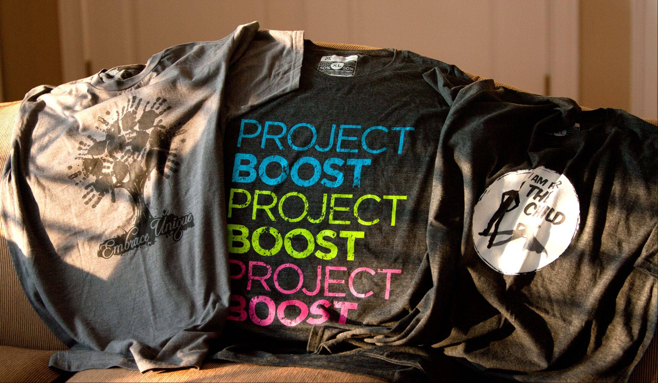 "ProjectBoost, founded by Glen Ellyn resident Shaun Emerson, develops and markets T-shirts for local nonprofits. Some of the shirts include the ""Embrace Unique"" design for Kaitlin's Hideout in Glen Ellyn, left, and ""I Am For The Child"" design for CASA of DuPage County, right."