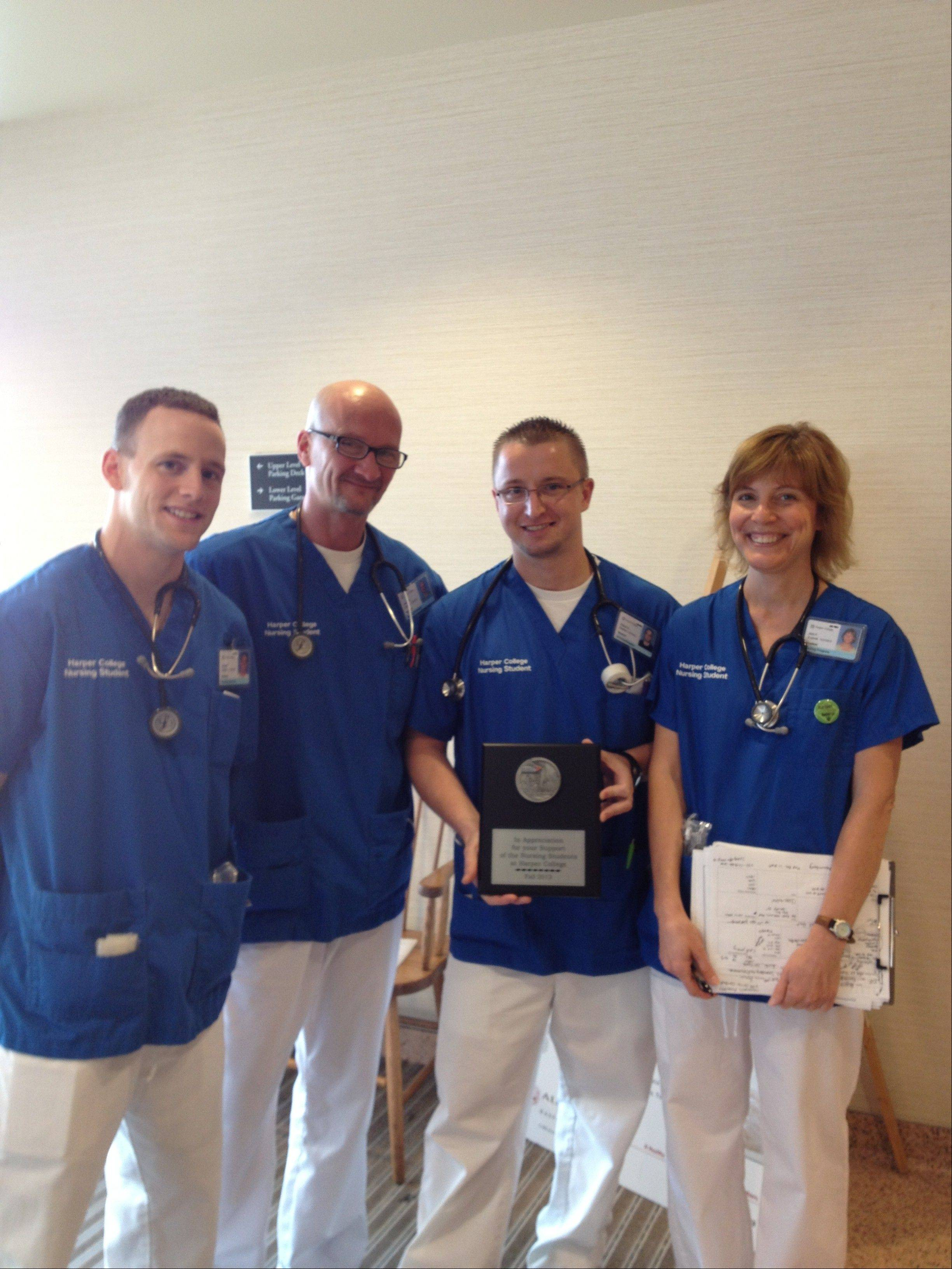 Nursing students, from left, Joseph Brisbois, Jim Owen, Patryk Gusciora and Ann Portmann pose with the plaque that Gusciora had made from his Chicago Marathon medal in honor of the nurses at Northwest Oncology at St. Alexius Medical Center. All four will graduate in December.