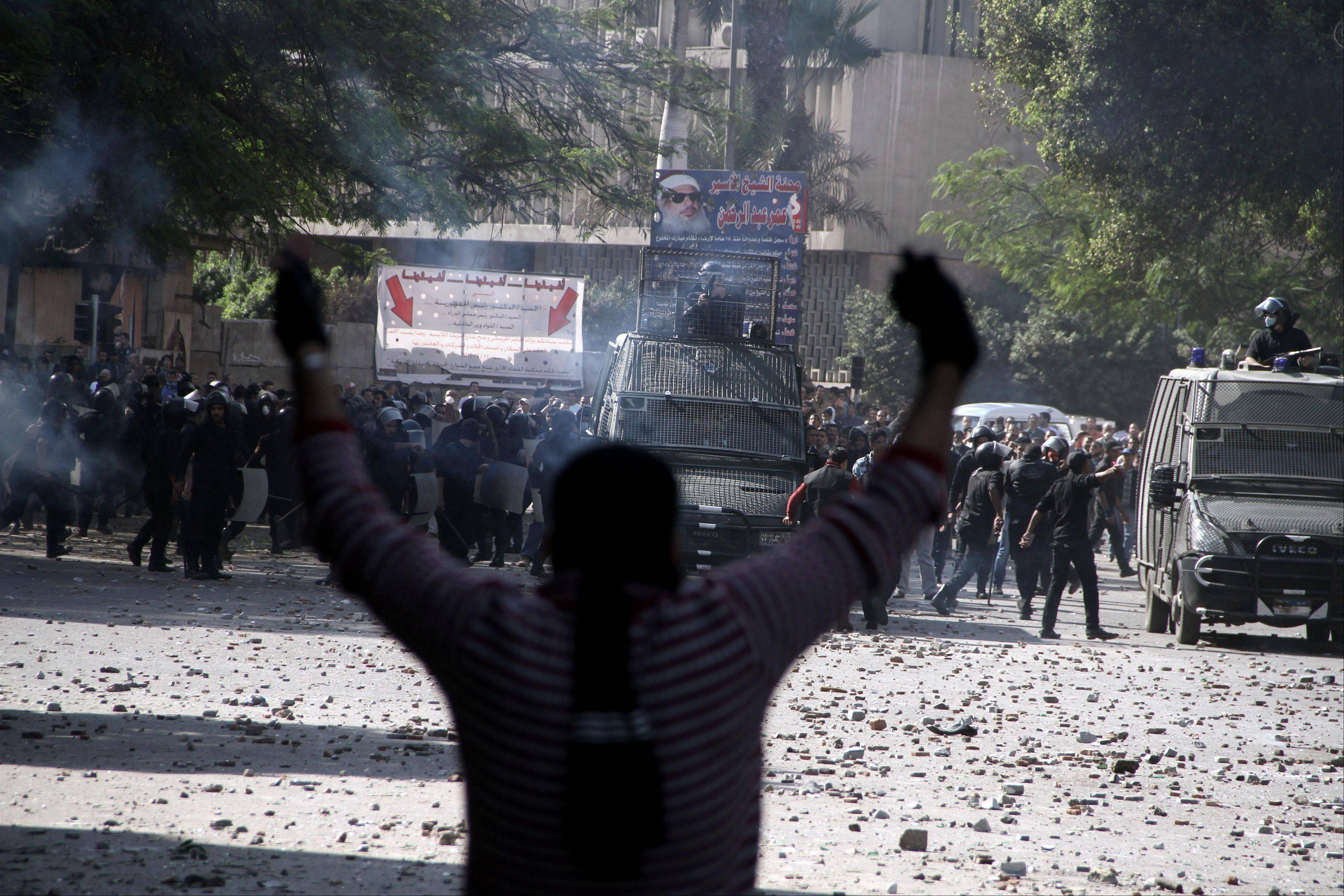 Egyptian security forces, background, clash with protesters near Tahrir Square in Cairo, Egypt, Sunday. Supporters and opponents of Egypt's president grow more entrenched in their potentially destabilizing battle over the Islamist leader's move to give himself near absolute powers, with neither side appearing willing to back down.