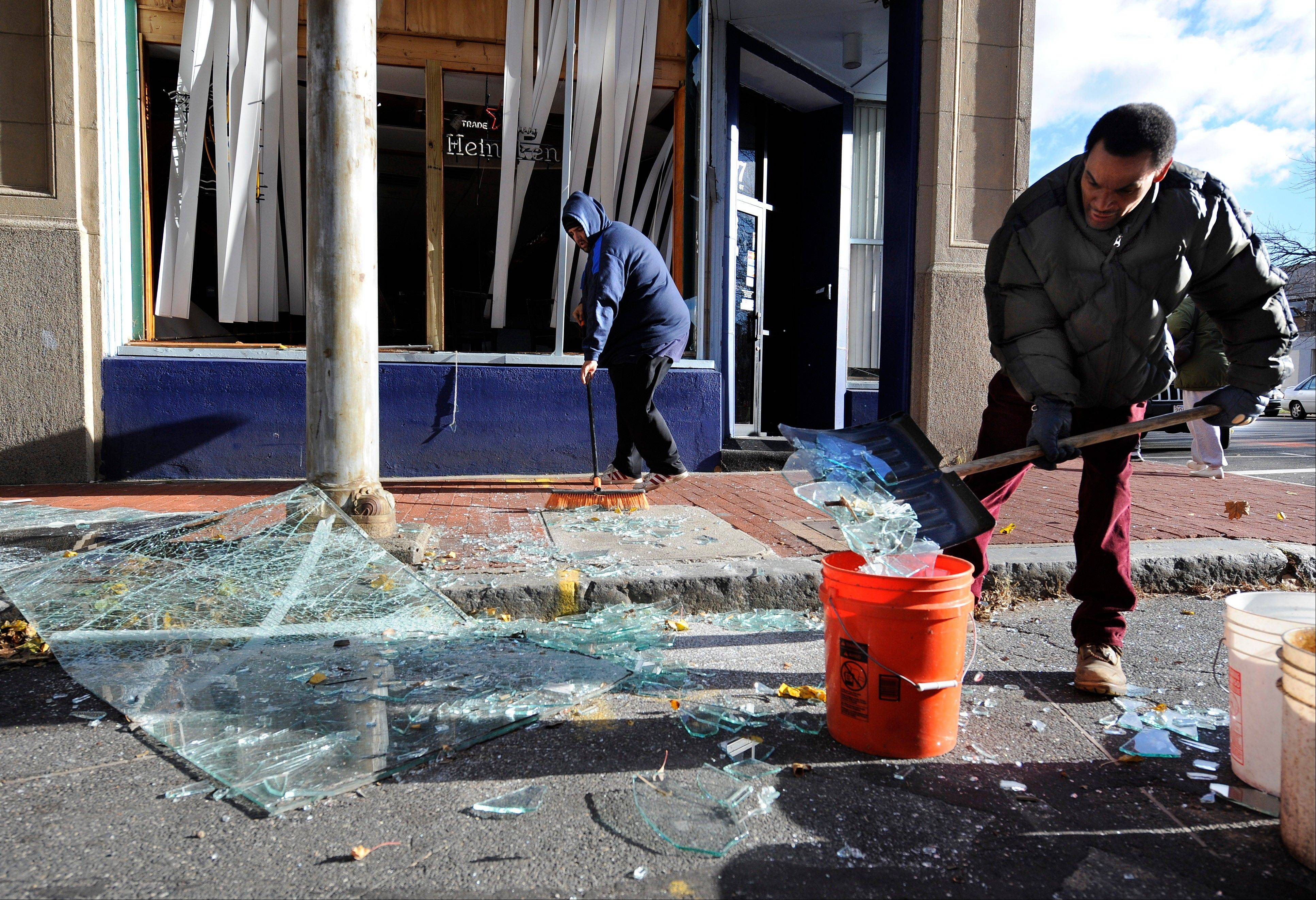 Robert Spano, left, and Alan Hugley clean up broken glass Saturday outside of Punta Cana Restaurant & Bar, a few blocks from the site of a Friday-evening gas explosion that leveled a strip club in Springfield, Mass.
