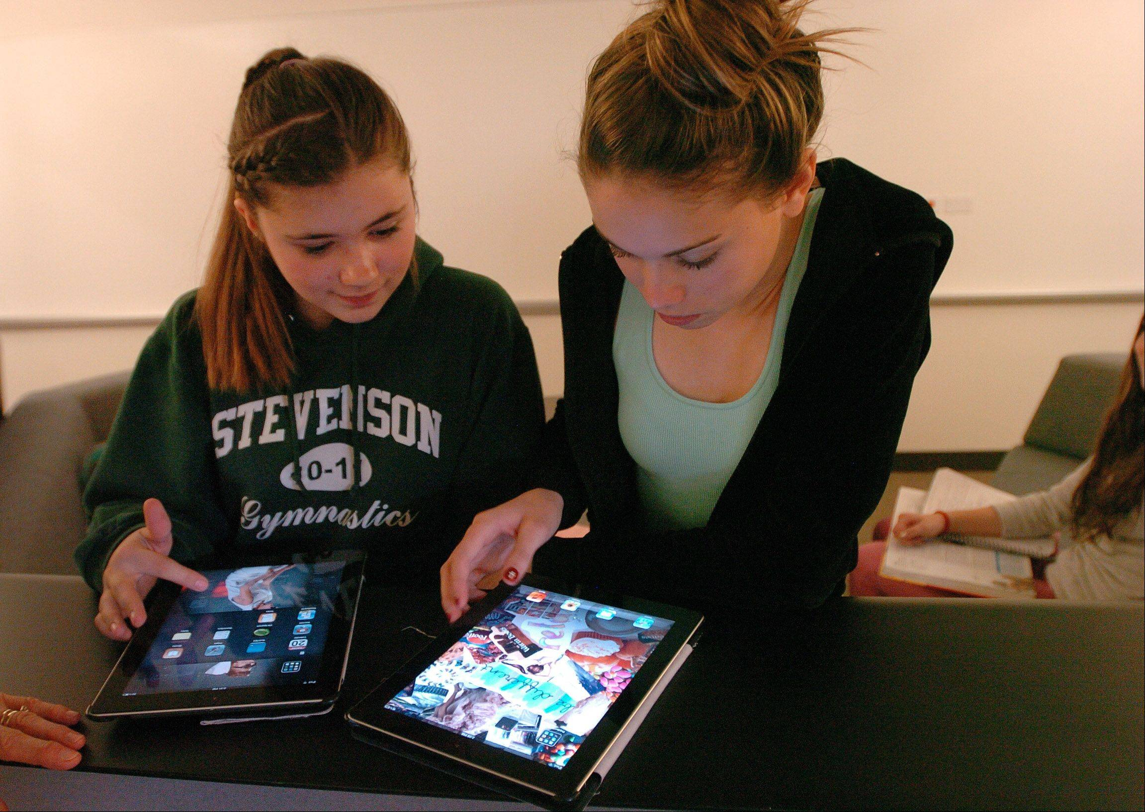 Freshman Spanish students Mikaela Webb, left, and Victoria Warren do homework on Apple iPad tablet computers.