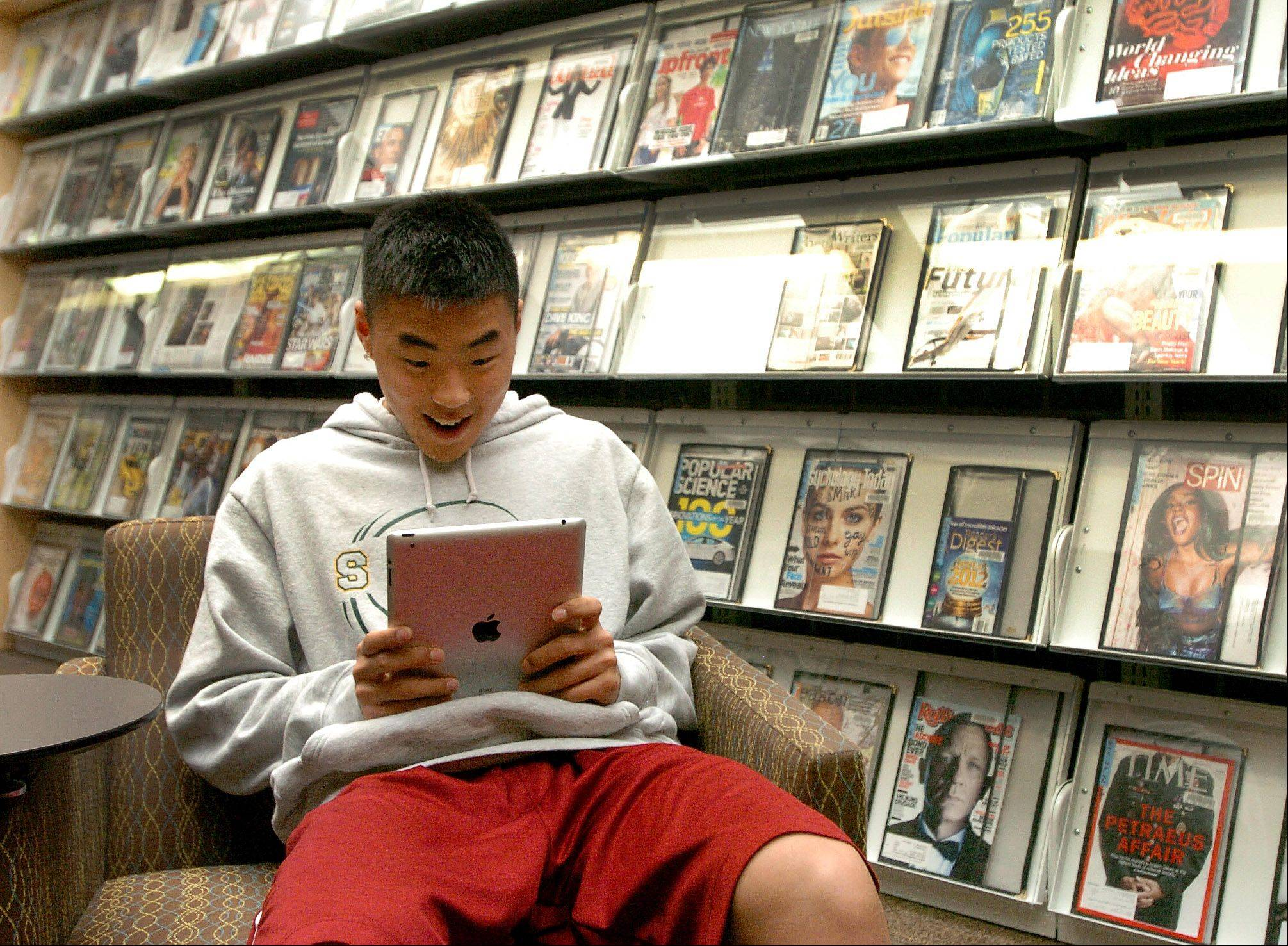 Sophomore basketball player Paul Yoon works with his Apple iPad tablet computer in the Information Learning Center at Stevenson High School.