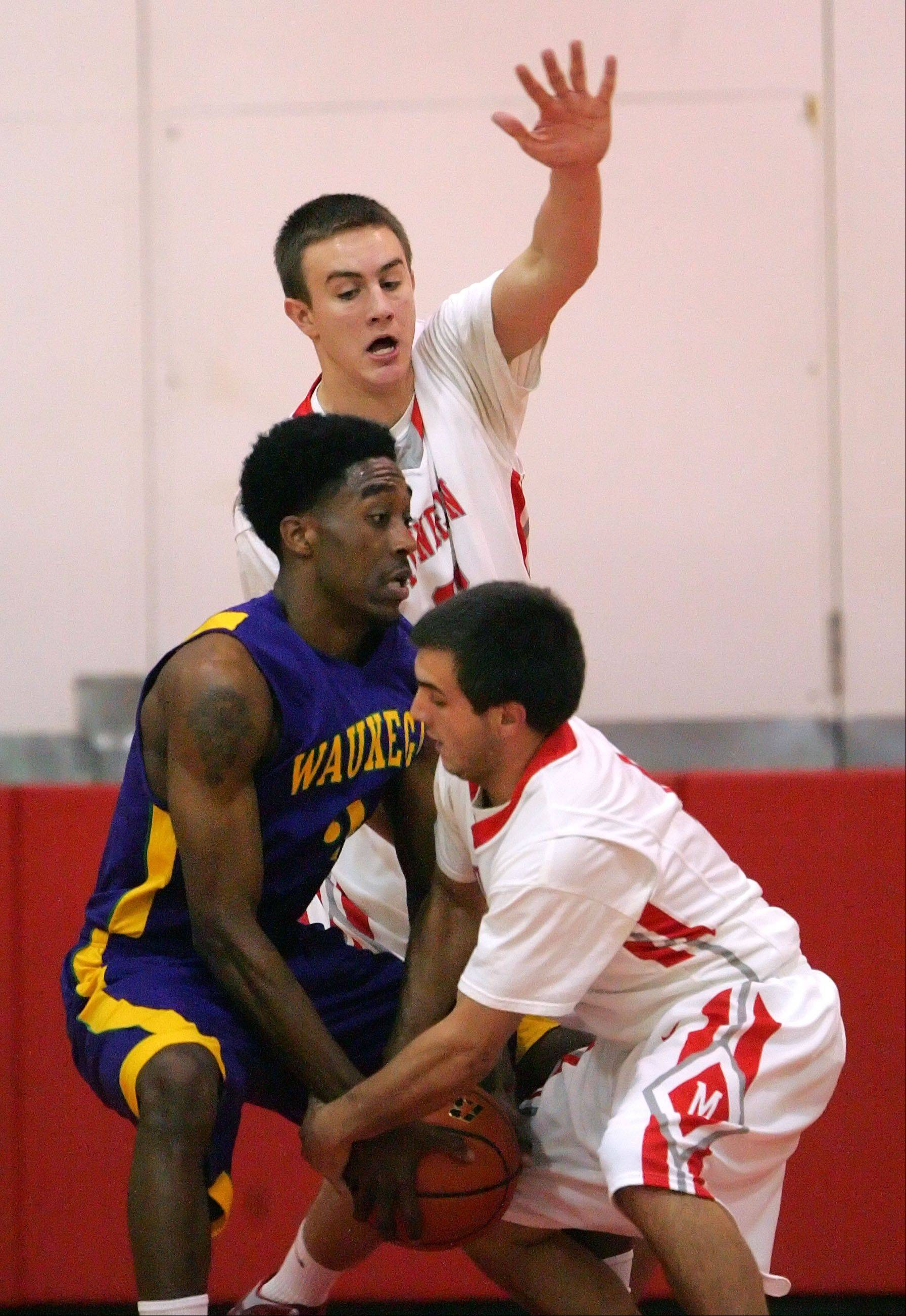 Mundelein's Sean O'Brien, back, and Thomas Gandolfi apply some tough defense against Waukegan's Cornell Fort during their game Friday night at Mundelein High School.