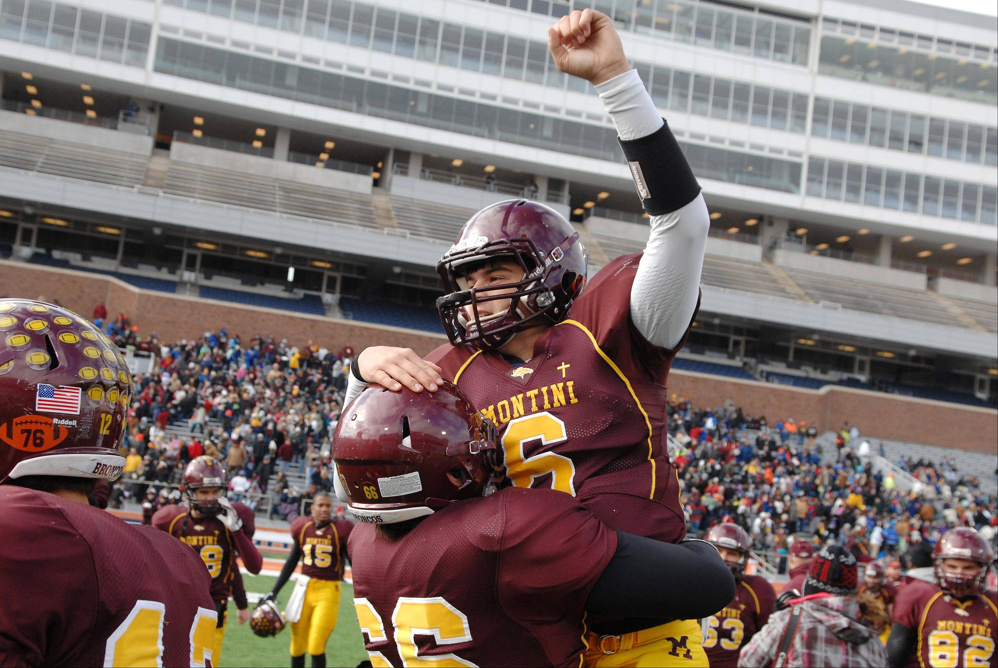 Montini quarterback Alexander Wills, 6, is hoisted in the air by teammate David Sarkan, 66, after their win over Morris in Saturday's Class 5A state title game at Memorial Stadium in Champaign.