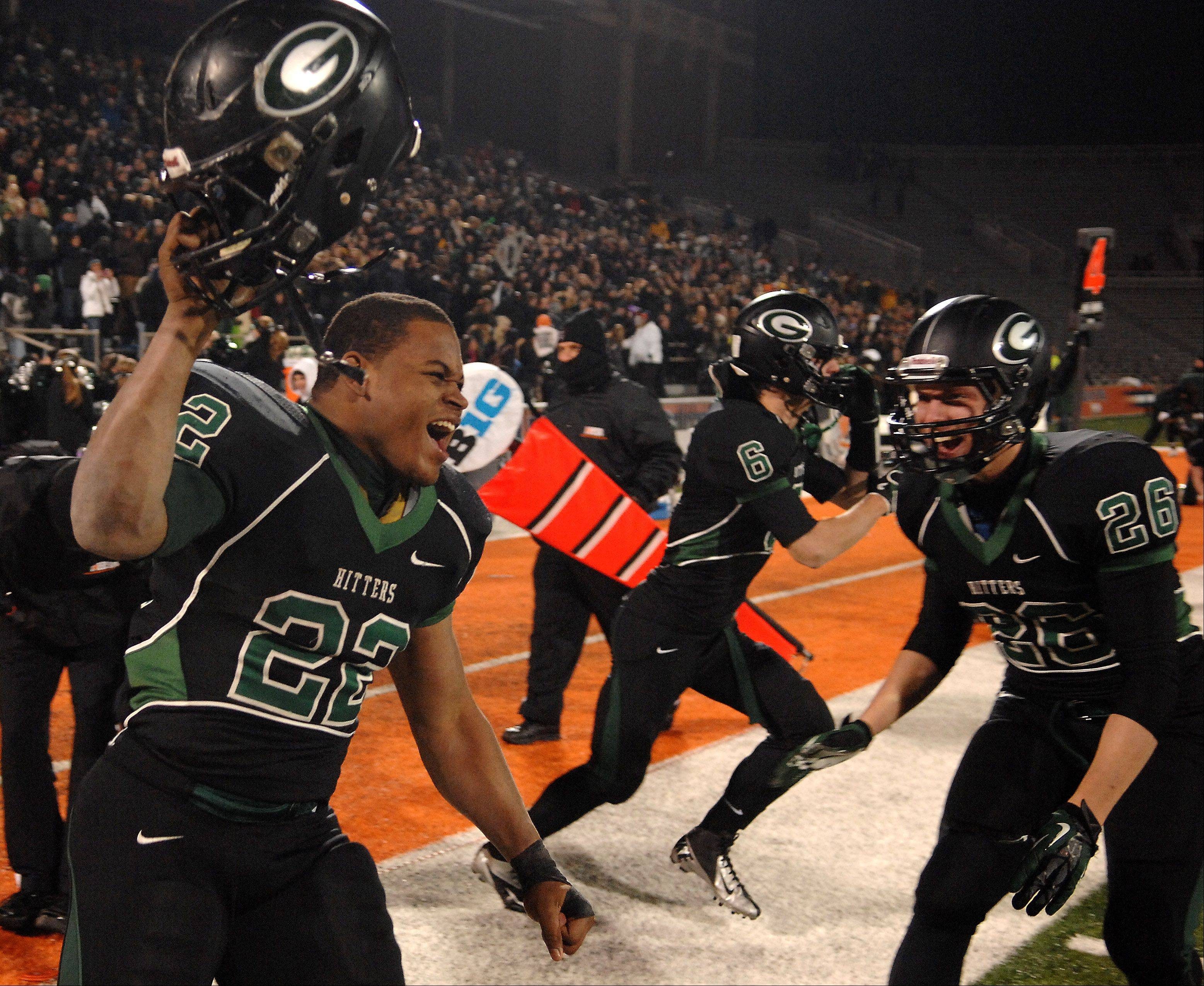 Glenbard West's Devante Toney, 22, and his teammates erupt in excitement as the defense stops Lincoln-Way East as the clock expires during Saturday's Class 7A state title game at Memorial Stadium in Champaign.