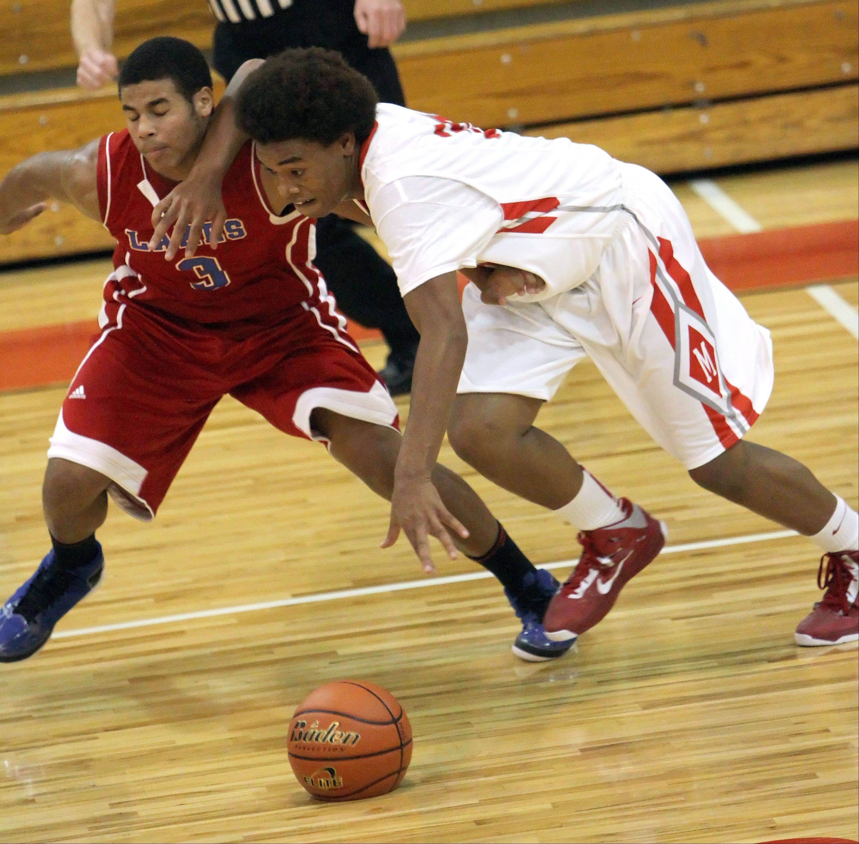 Mundelein's Nate Williams, right, drives on Lakes' TJ Edwards Tuesday night at Mundelein High School.