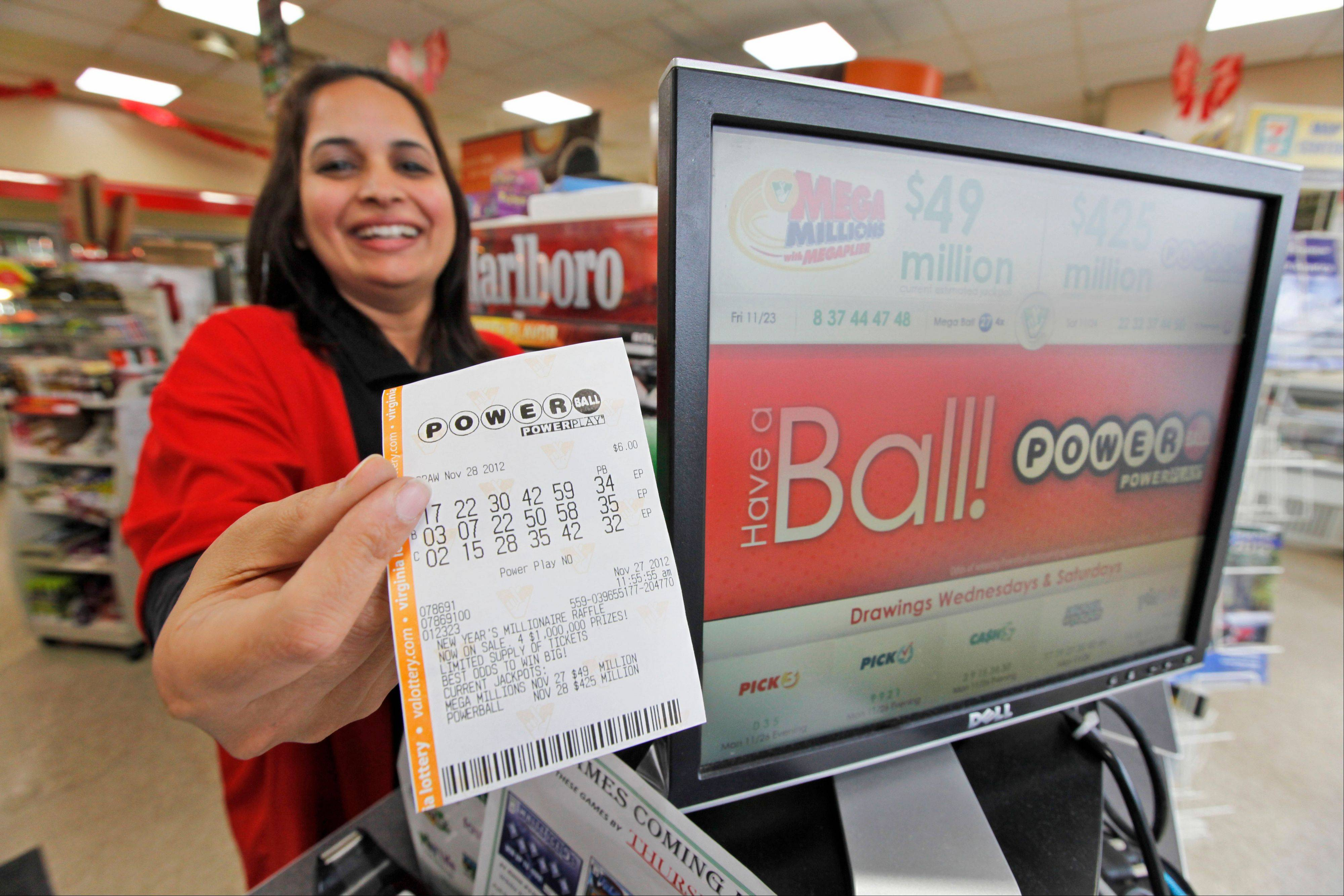 Cashier Farah Husain hands a customer a Powerball ticket at a convenience store Tuesday in Richmond, Va. The powerball jackpot is up over $500 million for Wednesday's drawing.